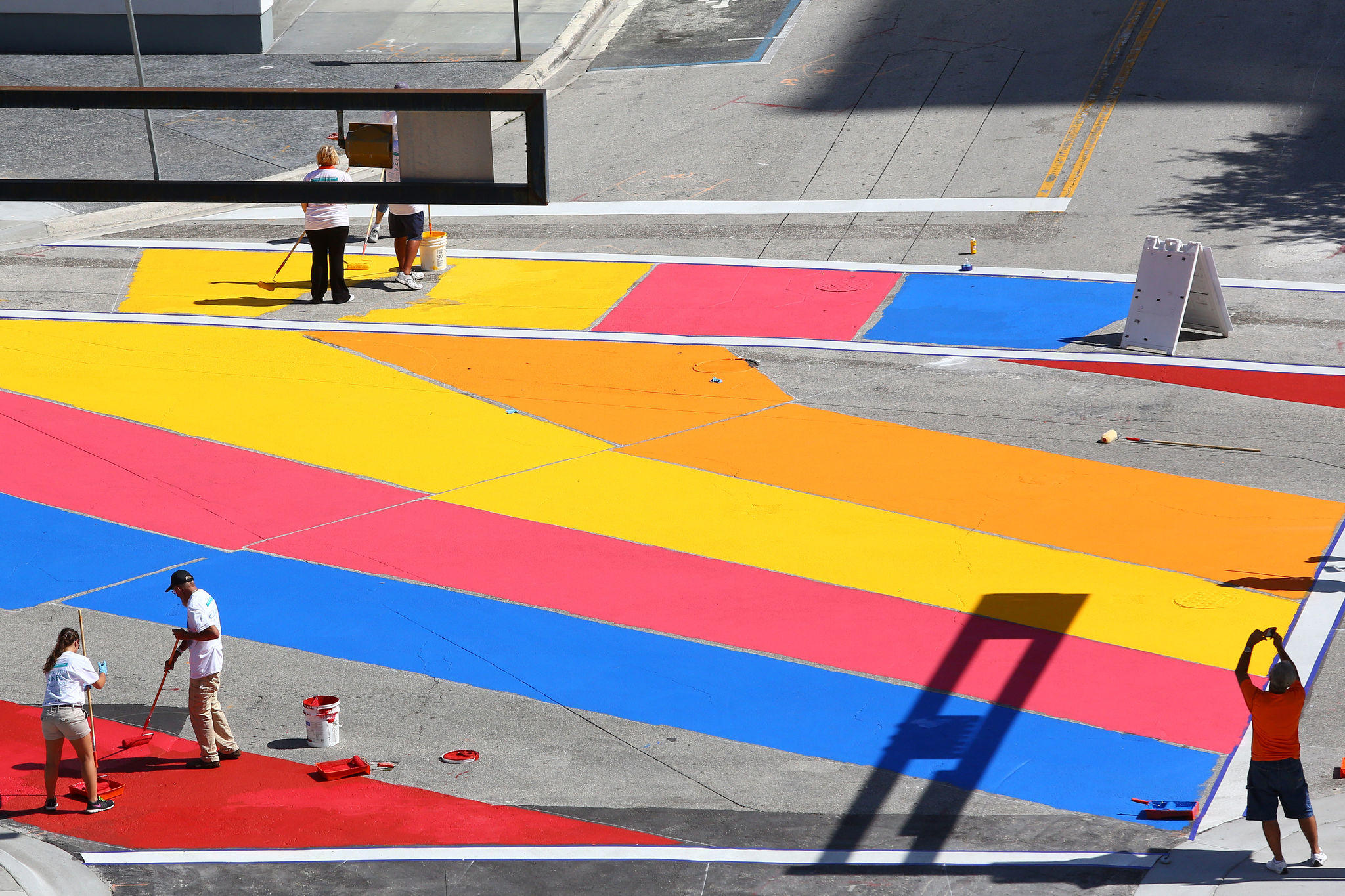 Volunteers paint over the intersection of Las Olas and SE 1st Avenue on Saturday with a colorful mural, a project by the city of Fort Lauderdale intended to add a splash of color to downtown and create a more pedestrian-friendly environment.