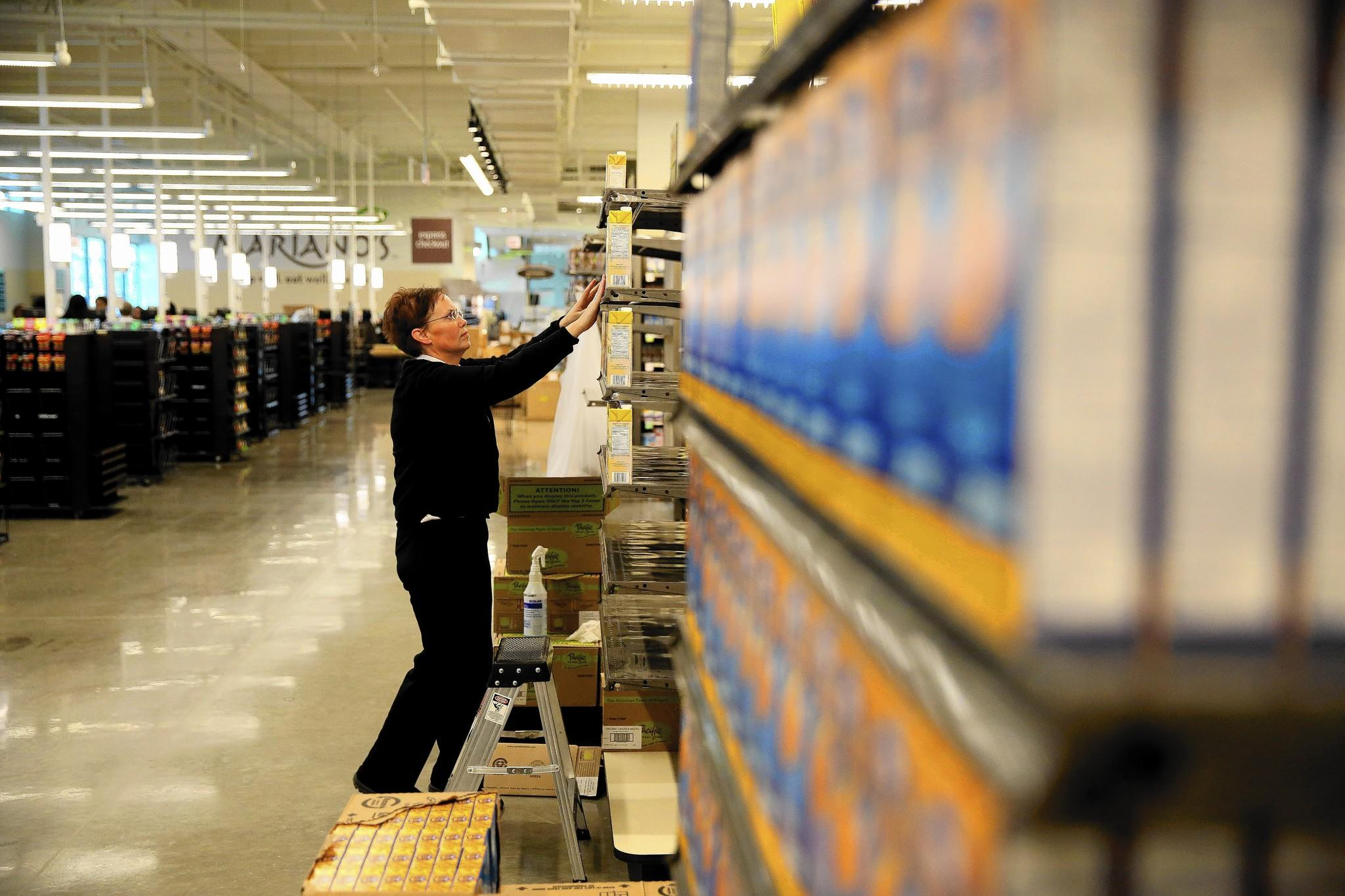Assistant manager Dana Higgs stocks shelves in preparation for the grand opening of a new Mariano's store at 2112 N. Ashland Ave.
