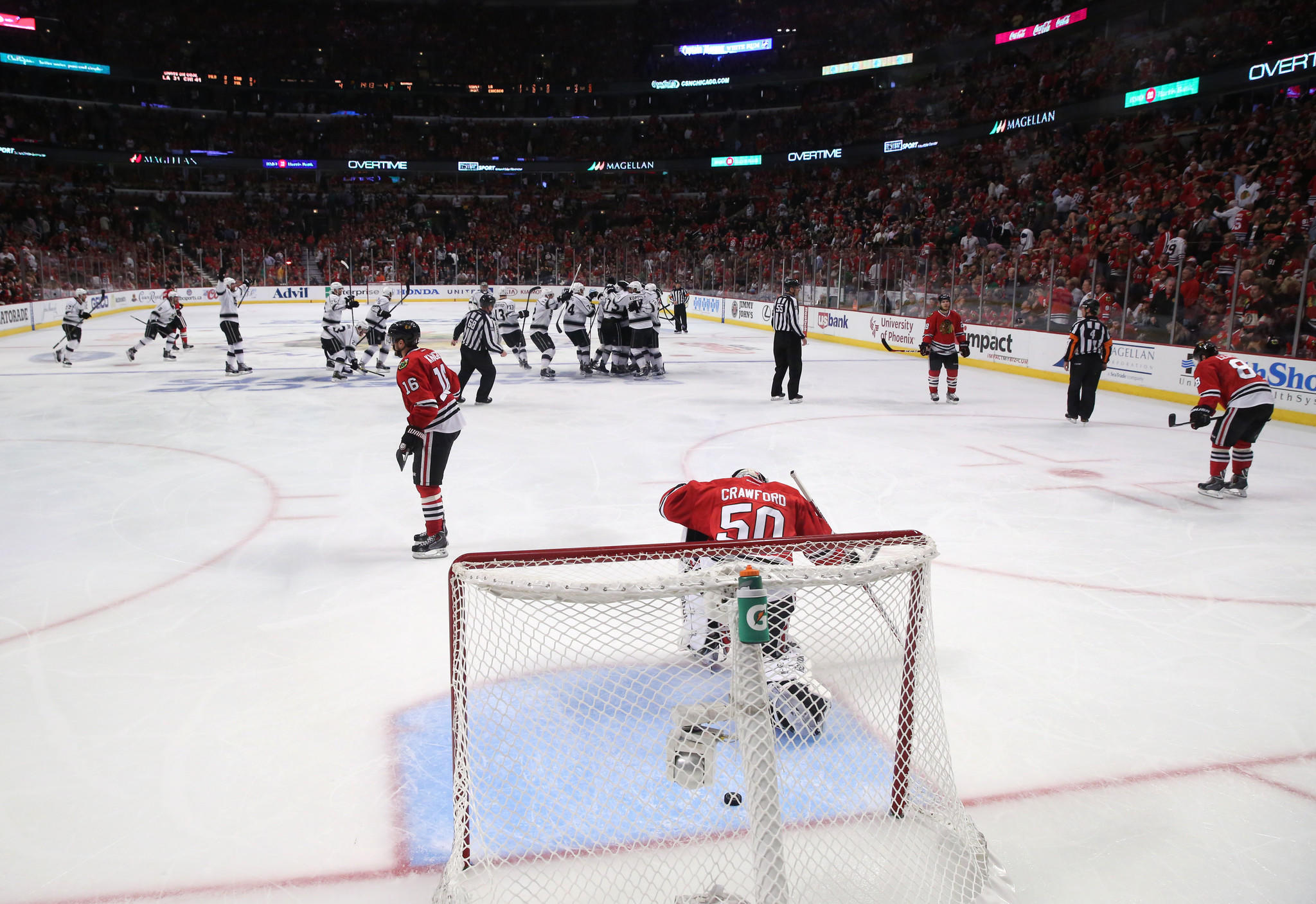 Corey Crawford kneels on the ice as the Los Angeles Kings celebrate in overtime.