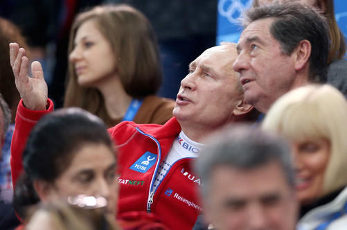 Russian President Vladimir Putin (red jacket) looks as perplexed as anyone watching figure skating as he joins ISU President Ottavio Cinquanta (right) at the 2014 Sochi Olympics.