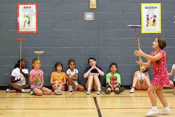 Campers and camp counselor Barbara Schiffer, center in purple, of Columbia watch as Peri Rose, right, of Westminster practices plate spinning during circus camp at Clemens Crossing Elementary School in Columbia, MD