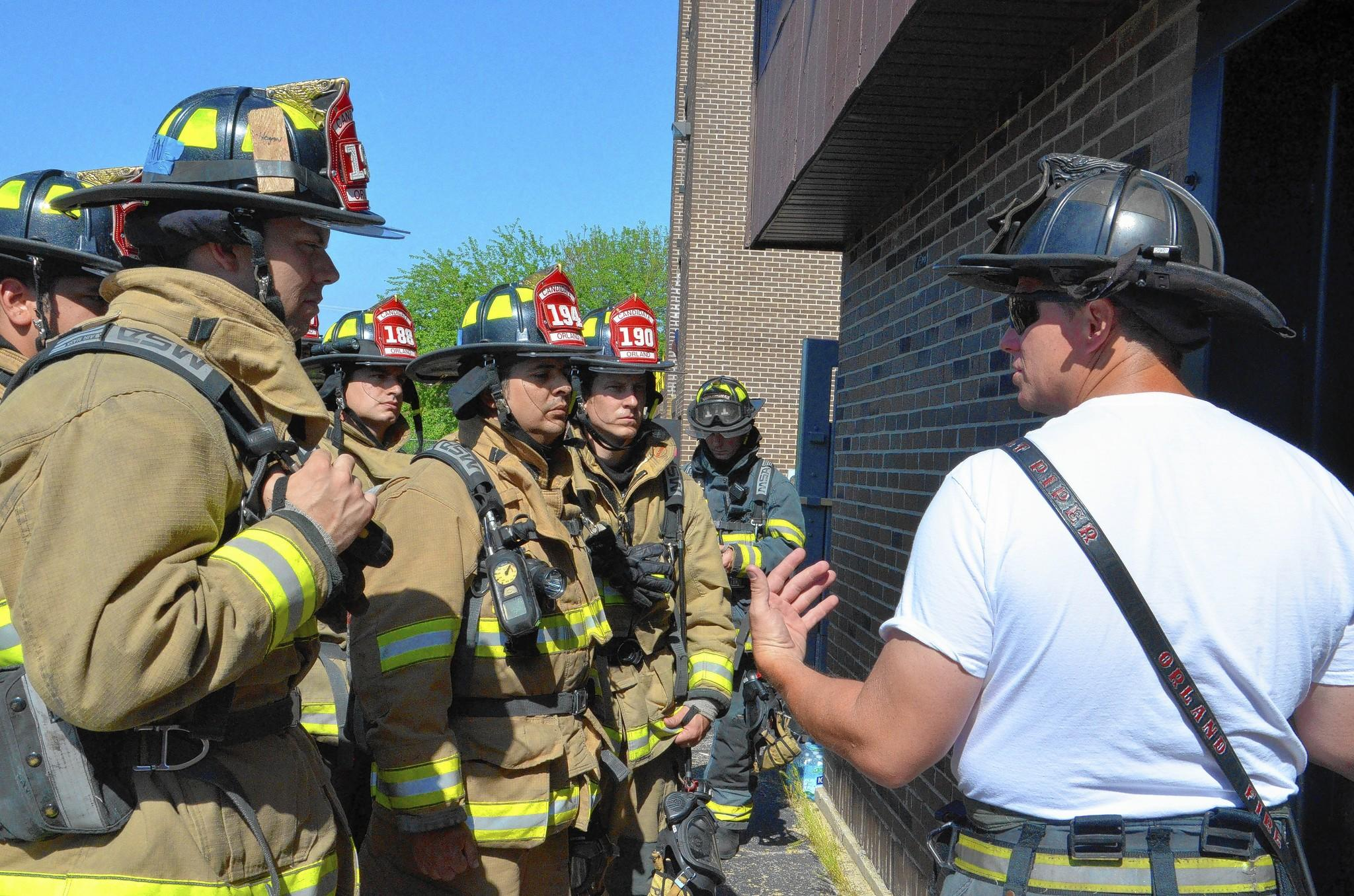 Lt. Dave Piper, training and safety officer at the Orland Fire Protection District, briefs candidates on the fire they're about to battle in a training exercise.