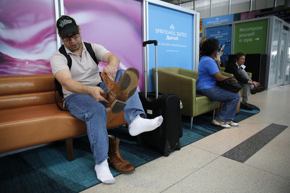 Traveler  Clyde Omar Torres of  New Orleans ties his boots while seated in a more comfortable, living-room-like seating area after going through a security checkpoint at O'Hare International Airport terminal 1.