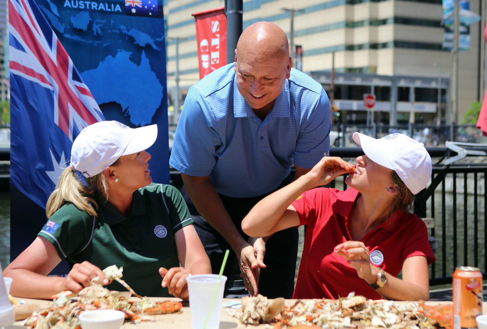 Baseball legend Cal Ripken, Jr., helps members Katherine Kirk (left) and Belen Mozo (right) of the Ladies Professional Golf Association crack crabs at Phillips Seafood on Pratt St. The event was used to promote the inaugural LPGA International Crown which will take place July 24-27, 2014 at Caves Valley Golf Club in Owings Mills.