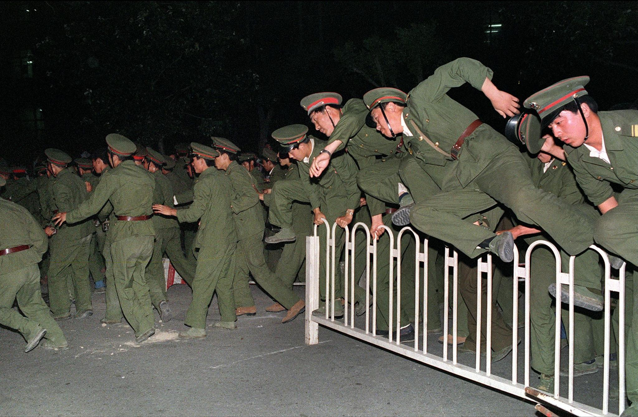 Liberation Army (PLA) soldiers leap over a barrier on Tiananmen Square in central Beijing in June 1989 during heavy clashes with people and dissident students.