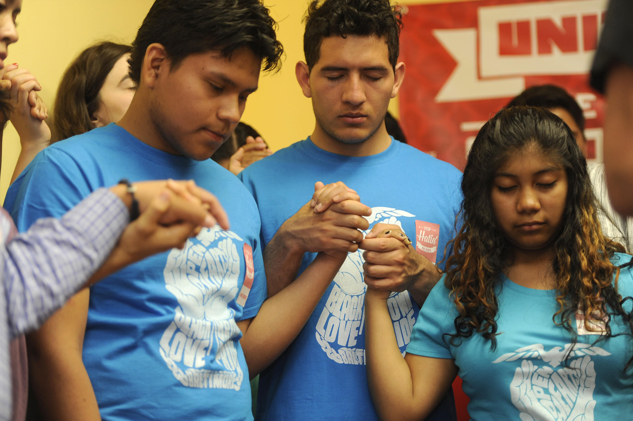 Left to right, praying at the end of a press conference: Jose Dominguez, Edwin Vasquez, Yanderi Hernandez. Representatives from hispanic and African American communities held a press conference at CASA de Maryland regarding ideas to prevent violence between the two communities.