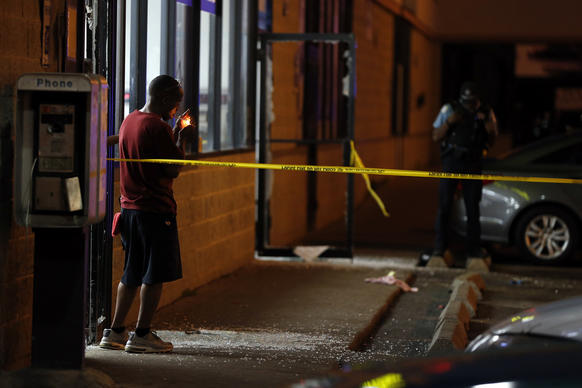 A man lights a cigarette as Chicago Police investigate a shooting at a laundromat on 79th Street in Chicago.