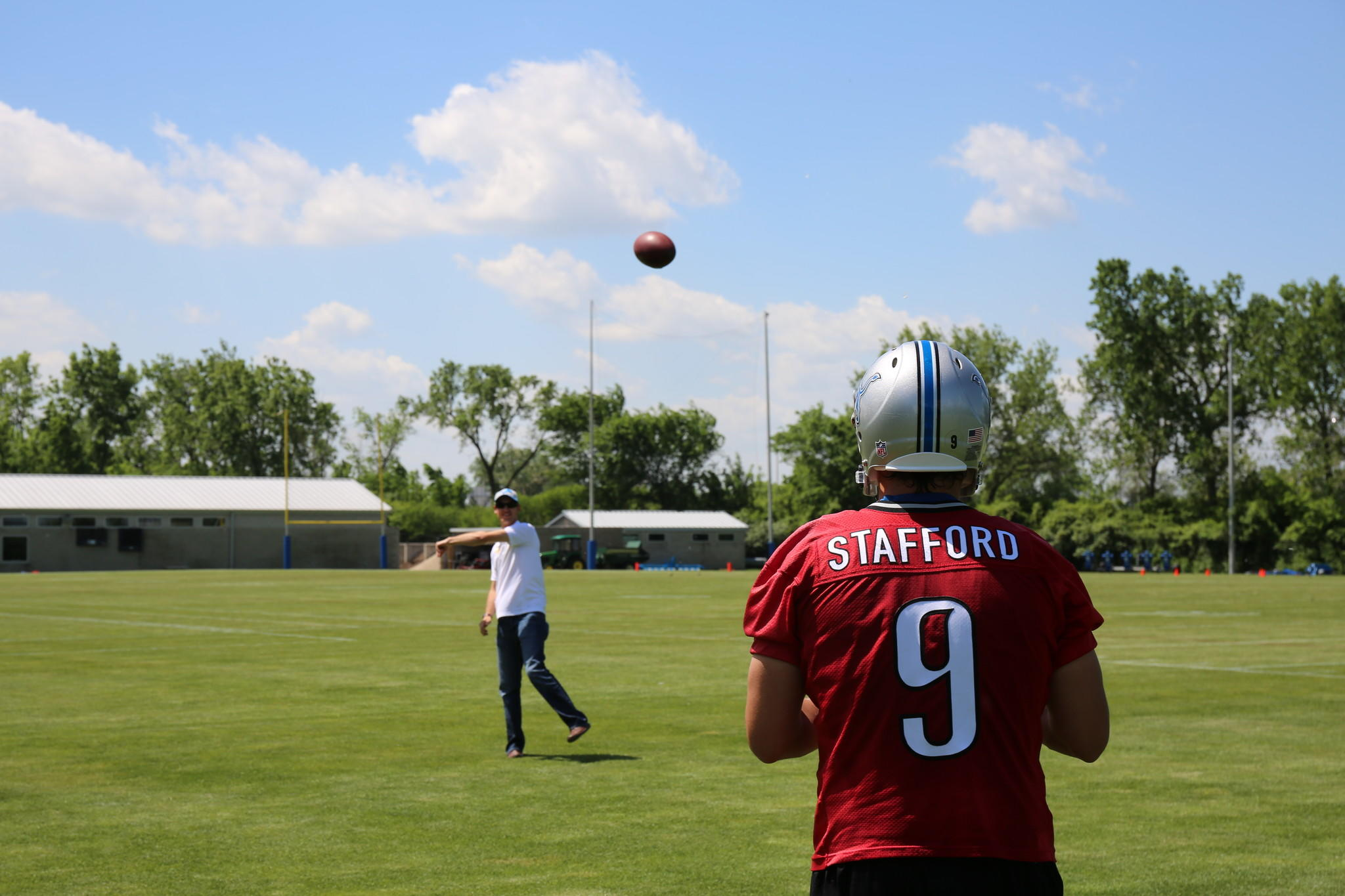 Joey Logano tosses the football around with quarterback Matthew Stafford. Logano stopped by the Detroit Lions' camp on Tuesday.