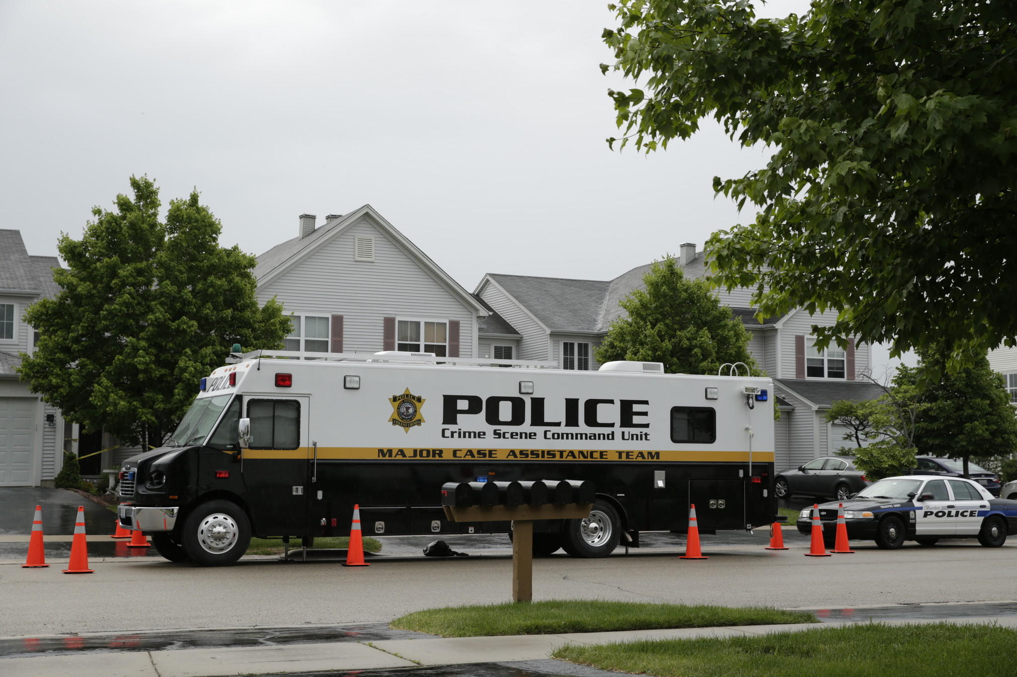 A Bartlett police car and the Police Crime Scene Command Unit sit outside of a town home in Bartlett where two people were found dead.