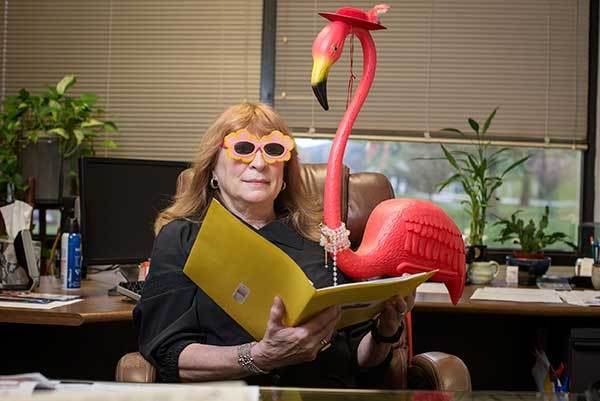 Nichole Hickey, the outgoing director of the Columbia Festival of the Arts, photographed with a plastic flamingo found at the Festival's headquarters at Columbia Lakefront.