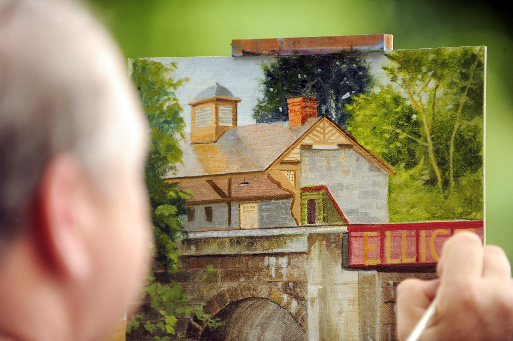 Sid Branham of Relay works on a painting of the historic Ellicott City train station and its surroundings during Paint It! Ellicott City.