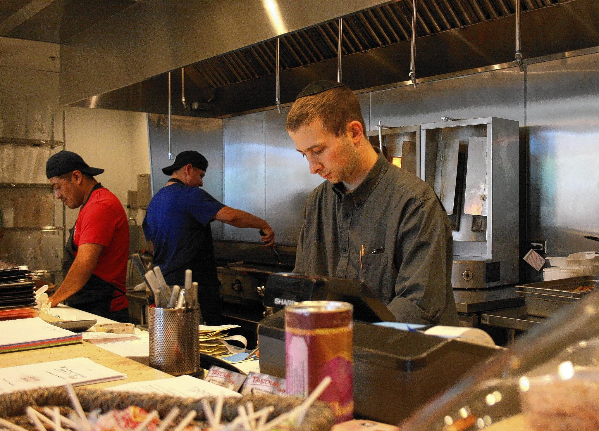 Eli Fagan, right, supervises the preparation of kosher food at the new location of Taboun Grill in Northbrook.