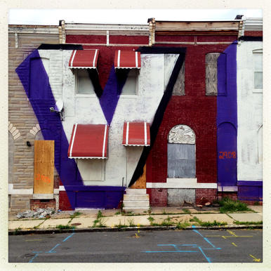 "A large ""V"" painted across abandoned rowhouses as part of the ""Forever Together"" mural on E. Eagers Street in Baltimore."