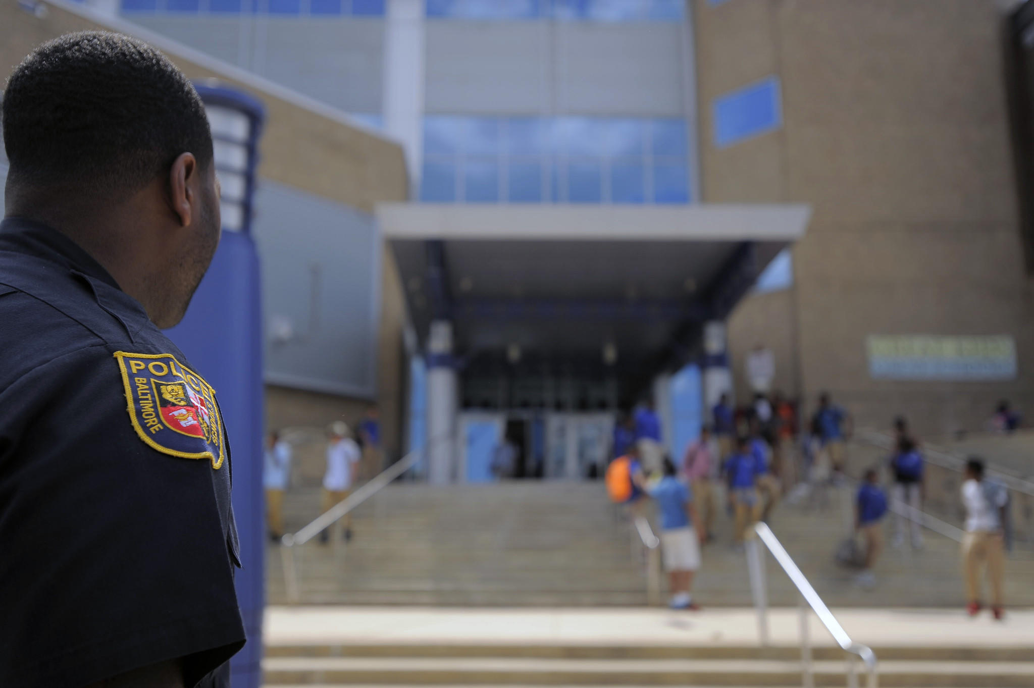 A Baltimore School Police officer observes the scene as school lets out.