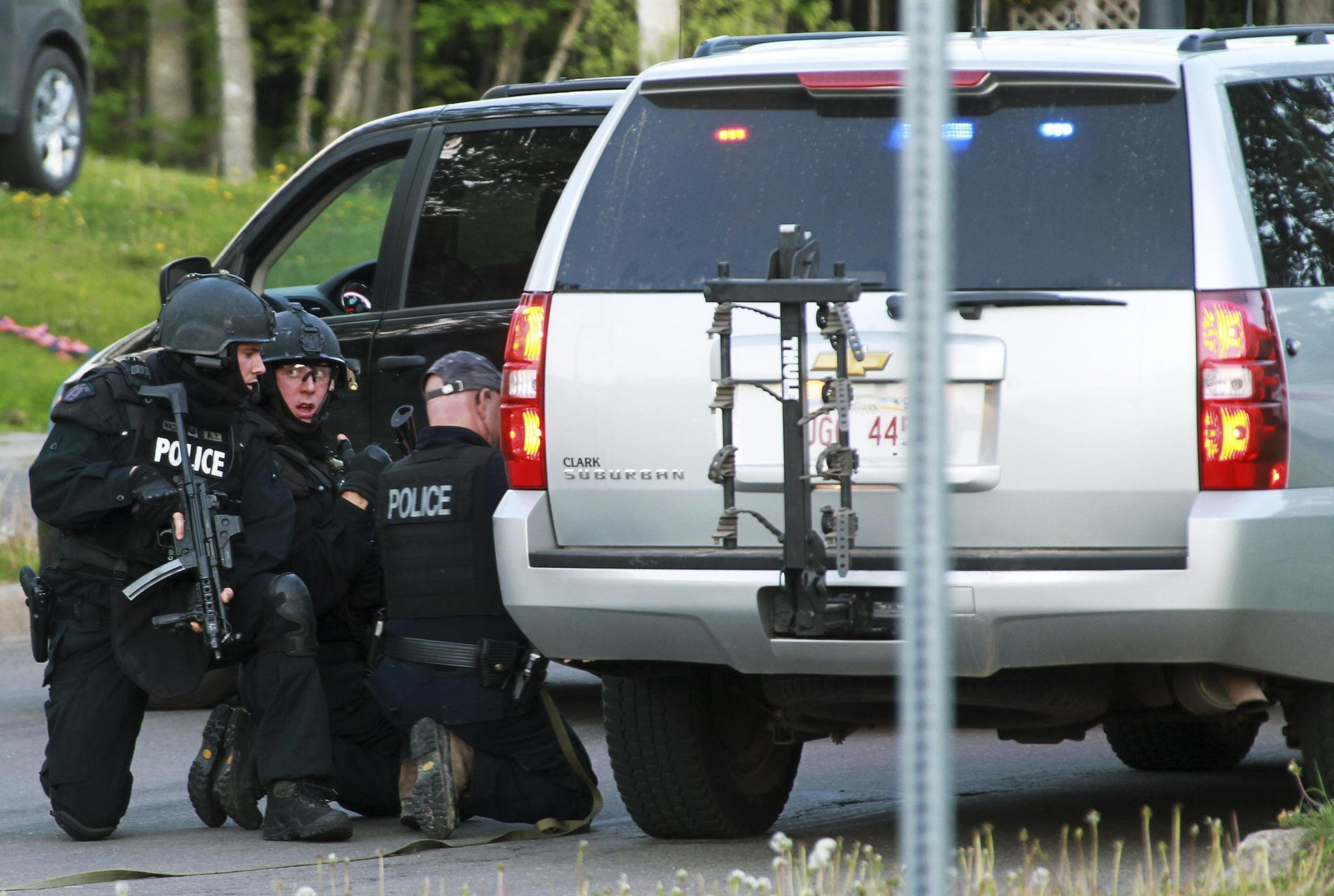 Emergency Response team members take cover behind vehicles in Moncton, New Brunswick June 4, 2014. Three police officers were shot dead and two more were wounded, police said as they conducted a manhunt for a man carrying a rifle and wearing camouflage clothes. Police said they were searching for Justin Bourque, 24, of Moncton.