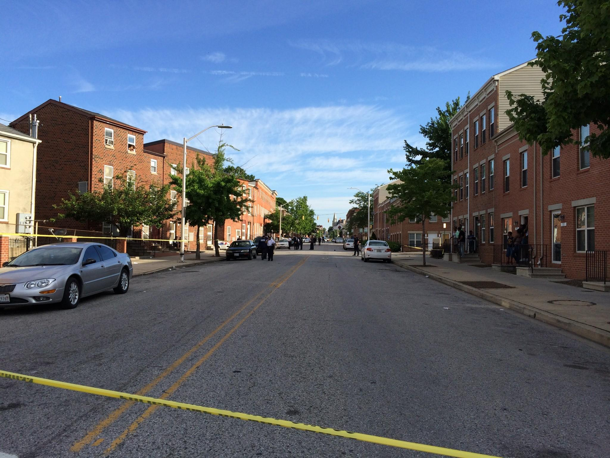Officers investigate the scene of a police-involved shooting in the area of West Fayette Street and North Fremont Avenue in Baltimore.
