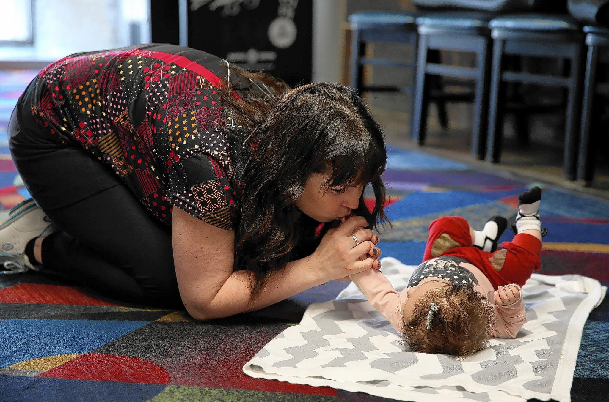 Diandra Asbaty, a professional bowler and mother of two, kisses her three-month-old baby Jersey Asbaty, before practice at the Diversey River Bowl.