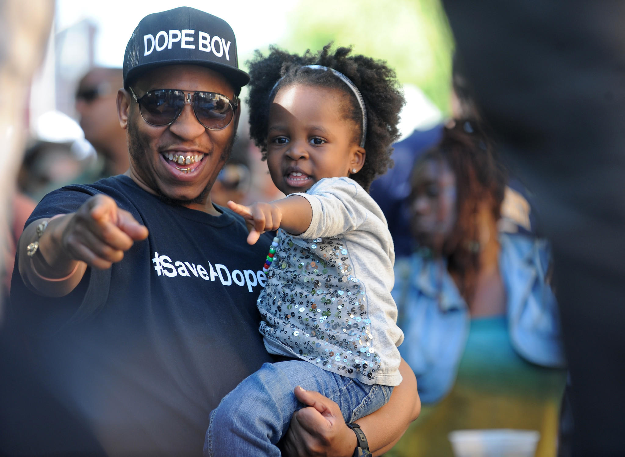 """Derrick """"OOH"""" Jones holds his daughter Neves Jones at the Sowebo Arts and Music Festival in 2013."""