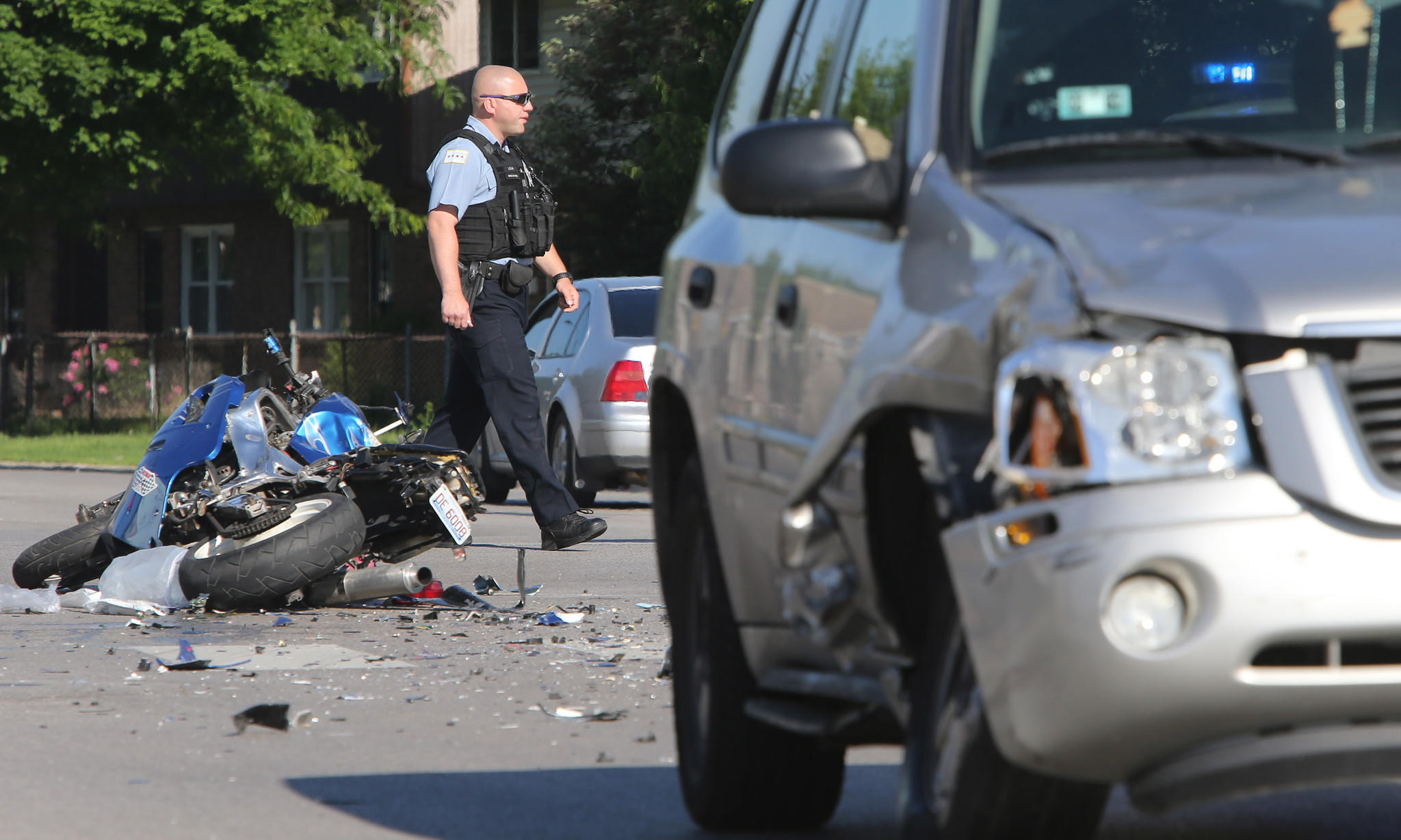 Police investigate the scene of an accident Friday morning involving a motorcycle and a GMC Envoy at the intersection of Washington Boulevard and Pulaski Road in Chicago.