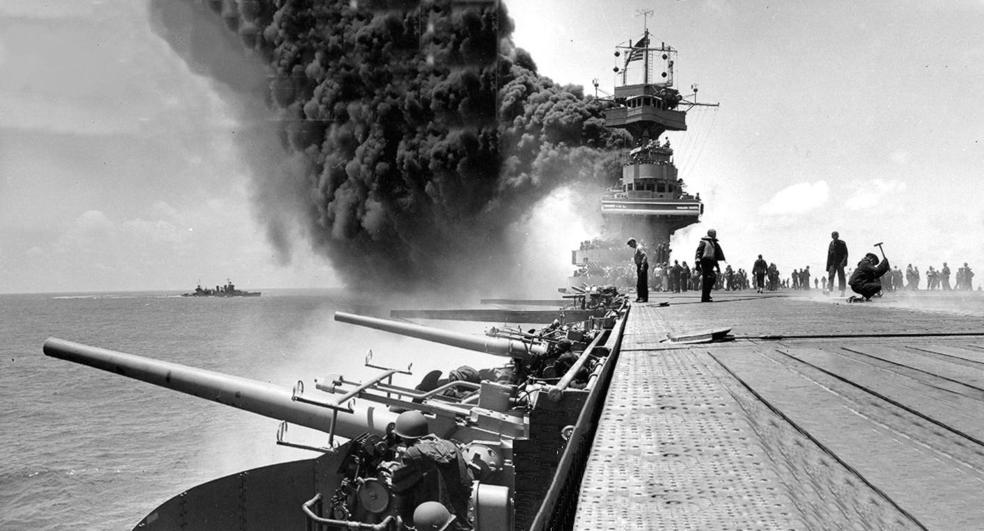 This view shows the giant plume of smoke coming from the USS Yorktown after it was attacked by Japanese planes during the Battle of Midway. The USS Astoria is shown in the left background.