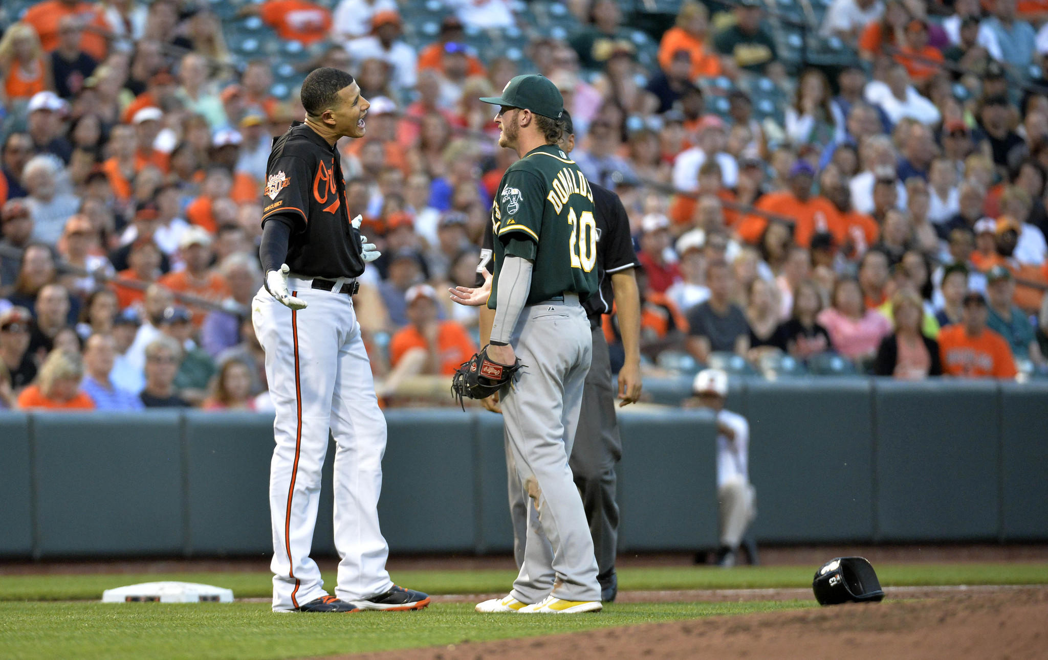 Manny Machado argues with Oakland's Josh Donaldson after being tagged out in the third inning.