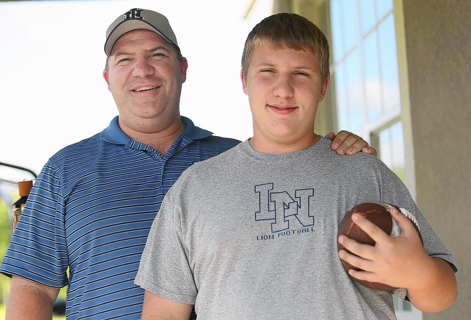 Tyler Albright, pictured with his dad Jeff, has suffered concussions playing football. The family has chosen for Tyler to continue playing football. They are picture at their Lake Nona home on Thursday, June 5, 2014.