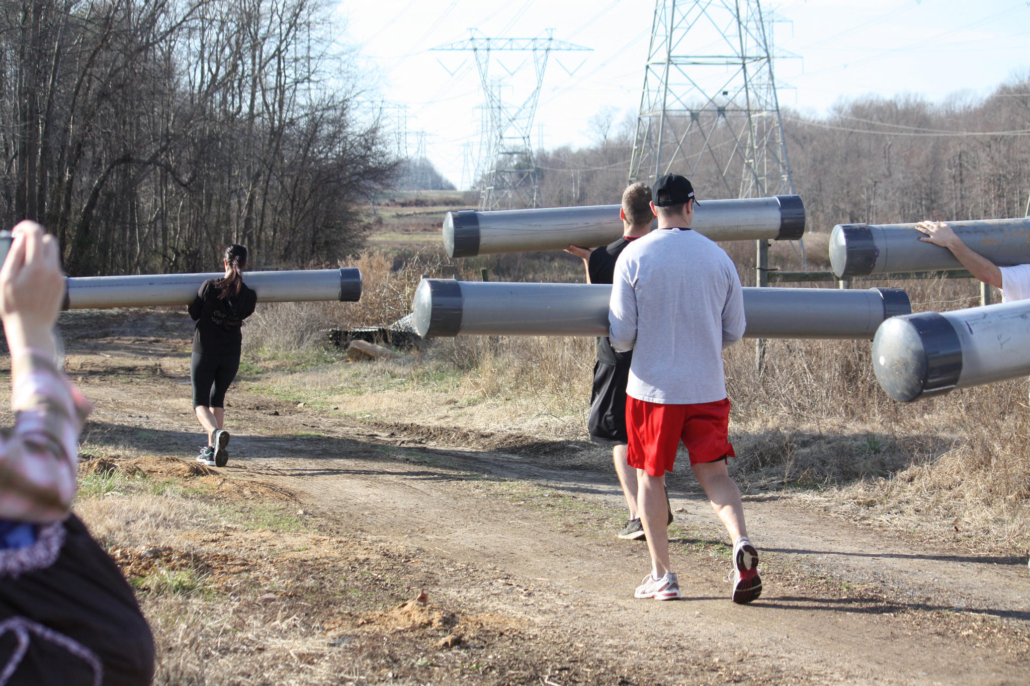 Water-filled tubes are carried by competitors during a training run for a siege race.