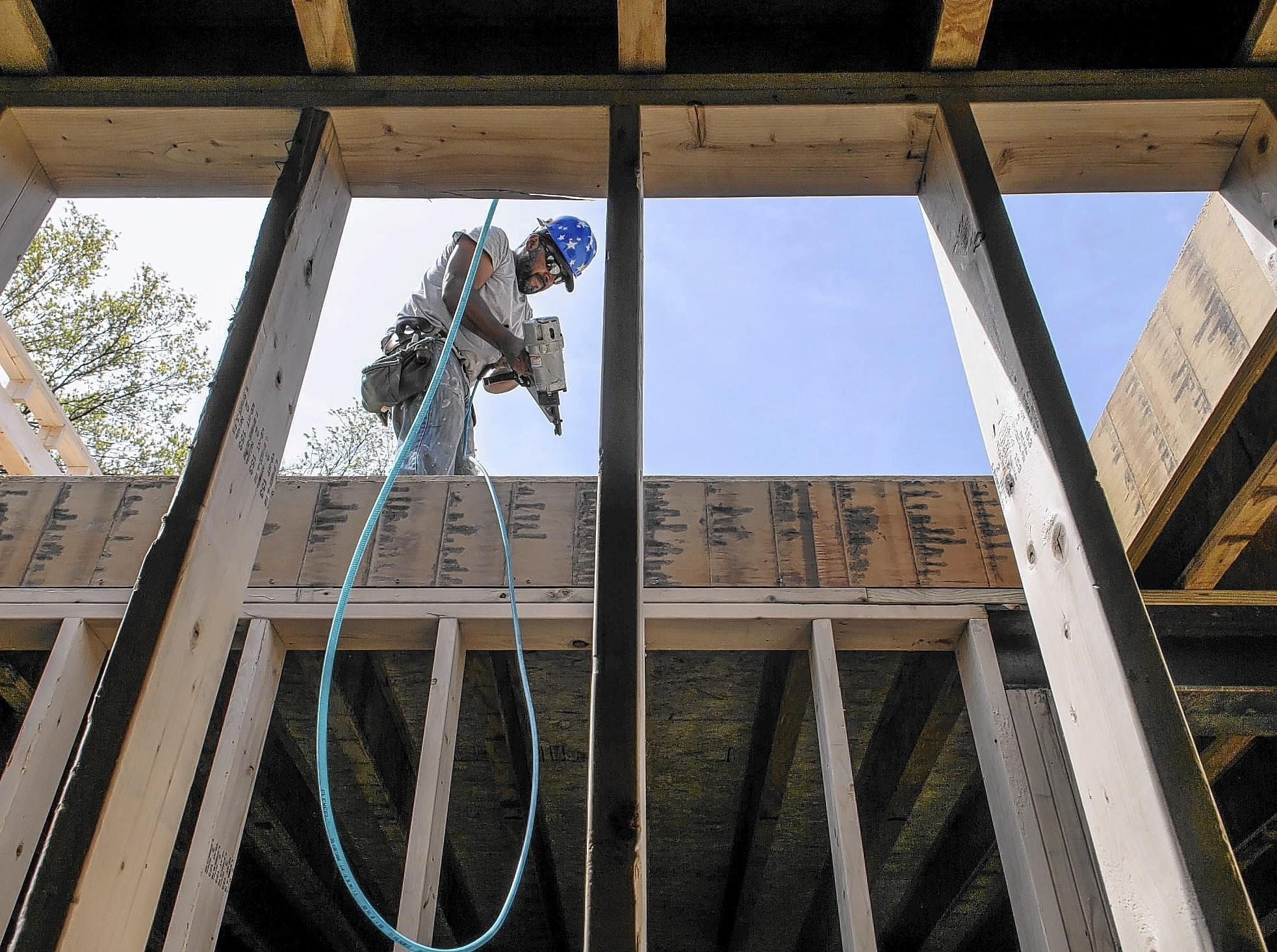 Wilman Zhunio frames a house in a Plainville development under construction.