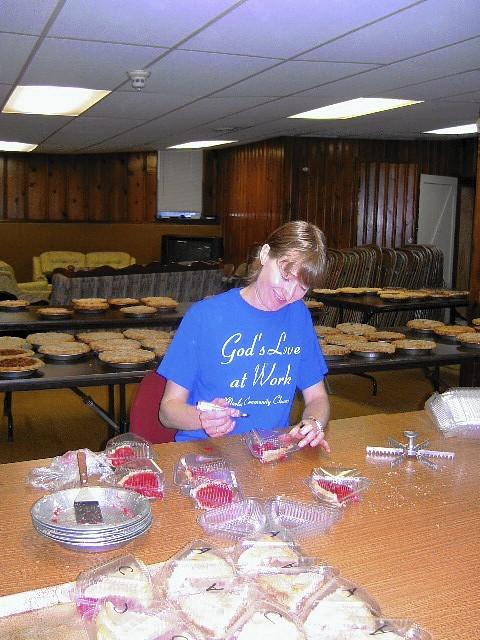 Janine White, a member of Marley Community Church, prepares pie slices to sell at a previous church fleamarket.