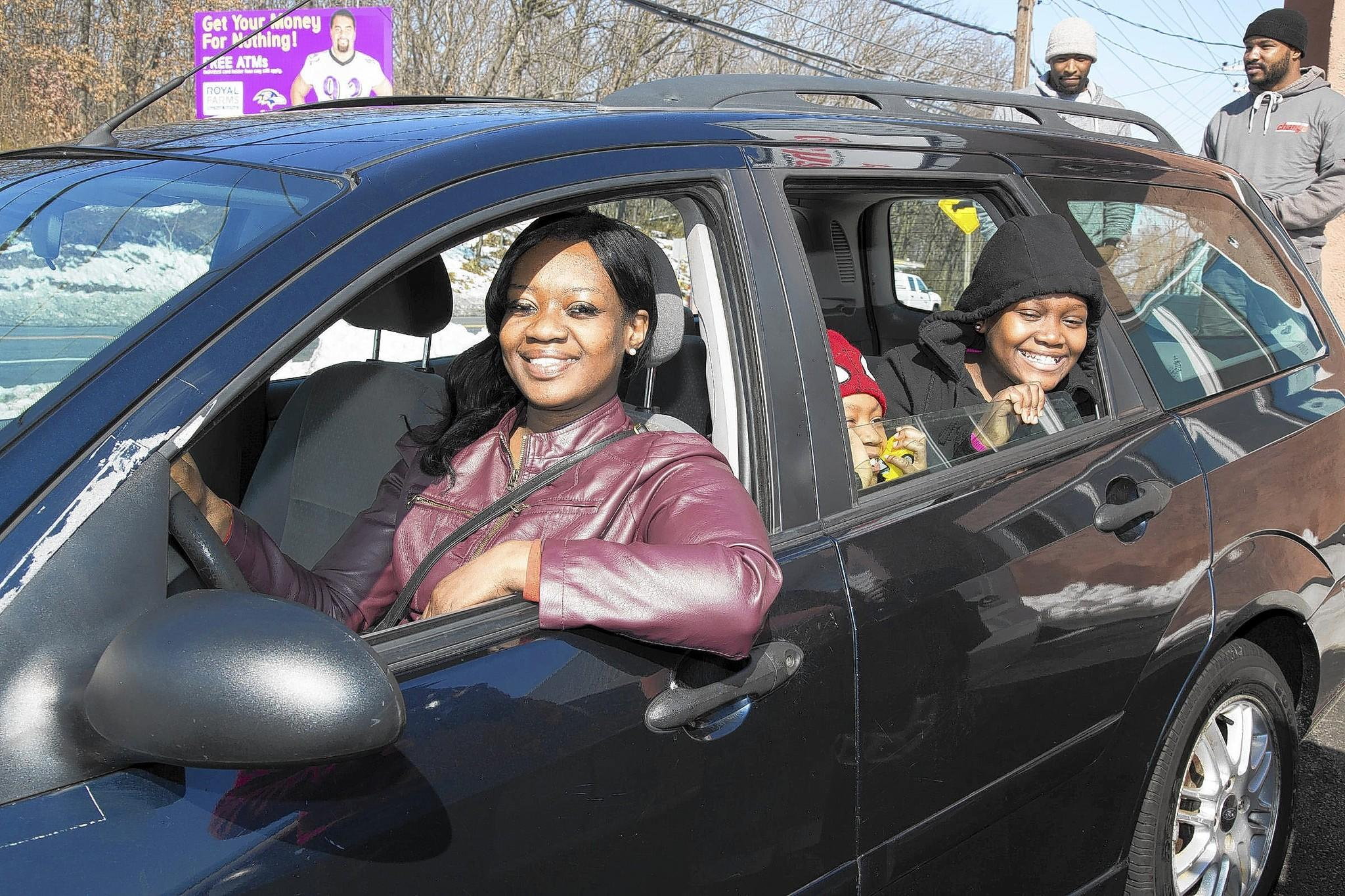 Vehicles for Change car recipient Krystal Parker and her family enjoy their new car.