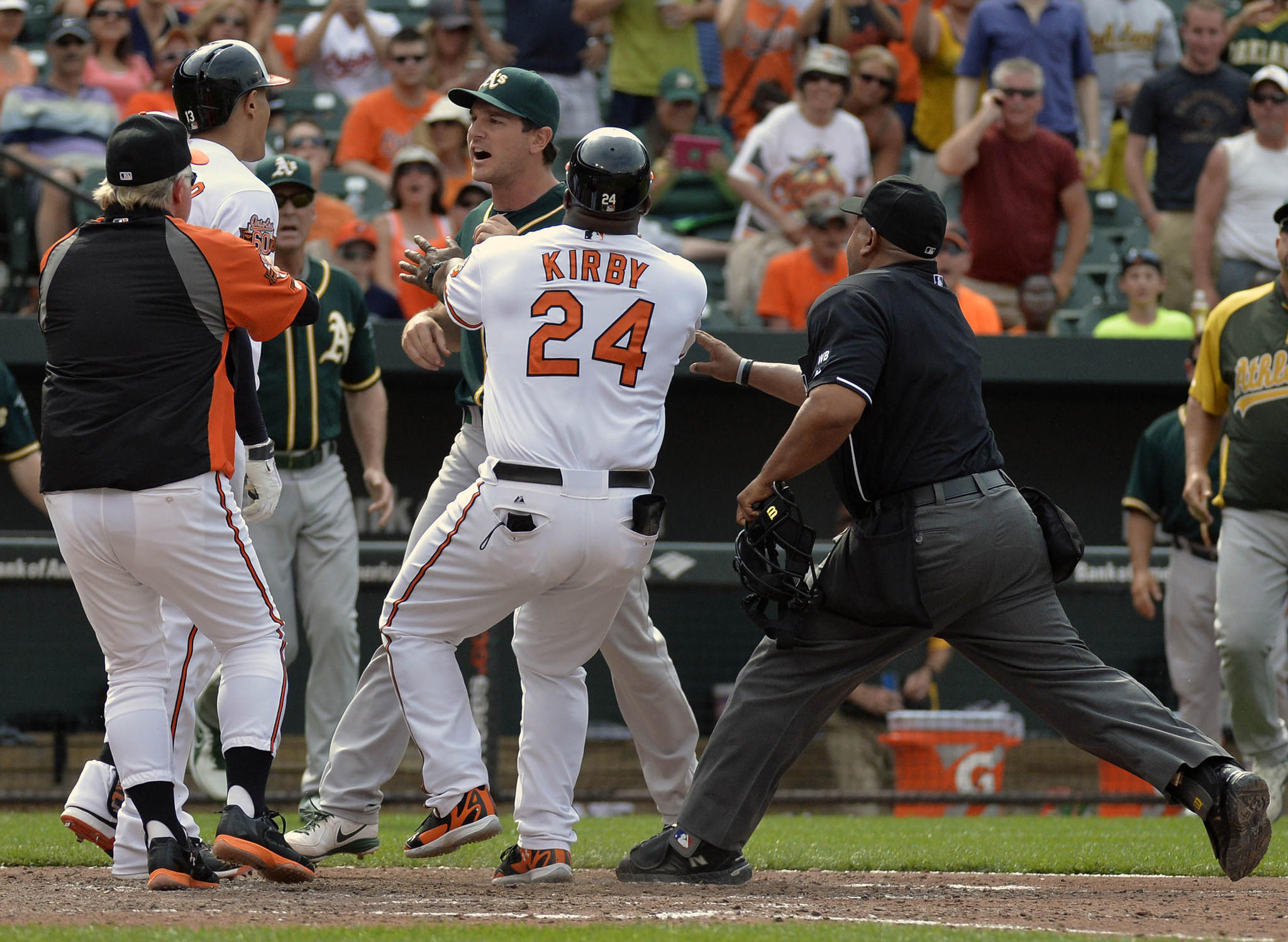 Orioles manager Buck Showalter, left, holds back third baseman Manny Machado, second from left, as first base coach Wayne Kirby, center, holds back an Oakland Athletics player in the eighth inning at Camden Yards.