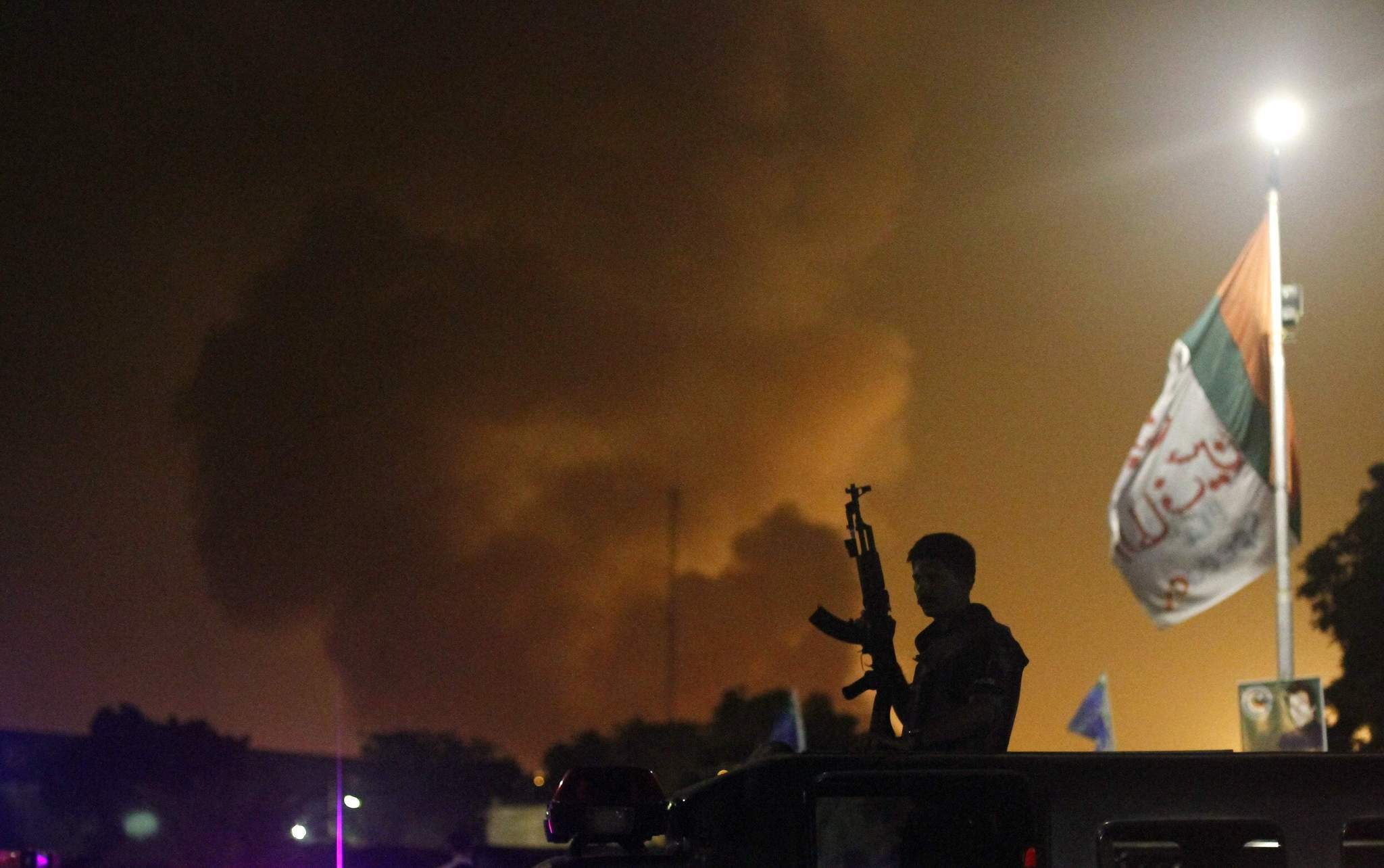 A police officer with a gun stands on a vehicle as smoke billows from Jinnah International airport in Karachi, Pakisant, on June 9.