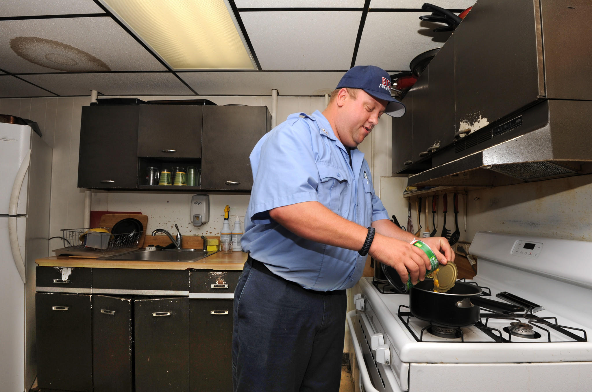 At Engine 57 on 4427 Pennington Ave., FFPM Brian Runge heats up canned corn for dinner.