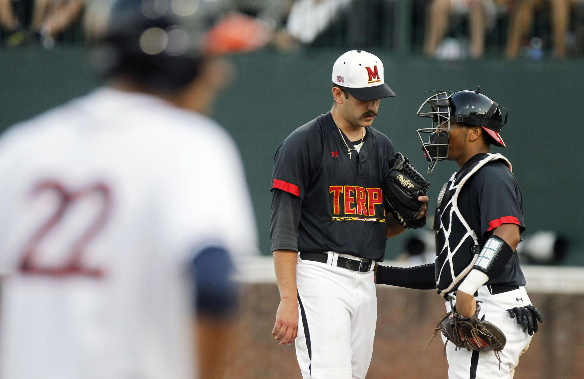 Maryland pitcher Bobby Ruse talks to catcher Kevin Martir as Virginia shortstop Daniel Pinero looks on from third base in the third game of the NCAA Super Regional.
