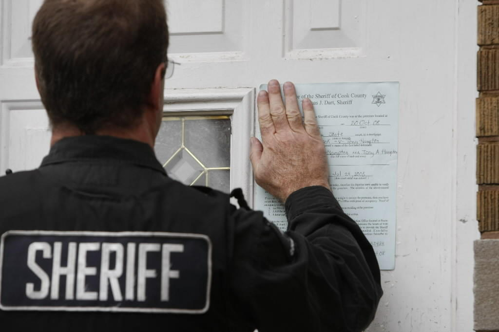 A sheriff's officer puts up notices on the door of a home in foreclosure in the Englewood neighborhood of Chicago.