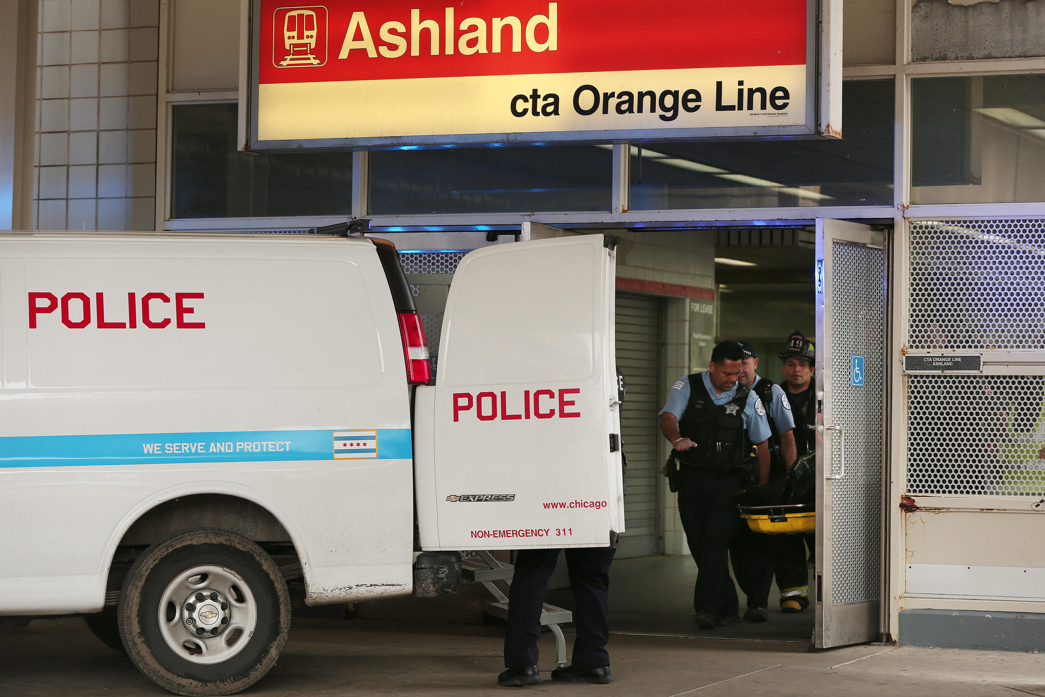 Police and firefighters transport the body of a man who was struck and killed by a CTA Orange Line train at the Ashland Avenue CTA Orange Line station in Chicago.