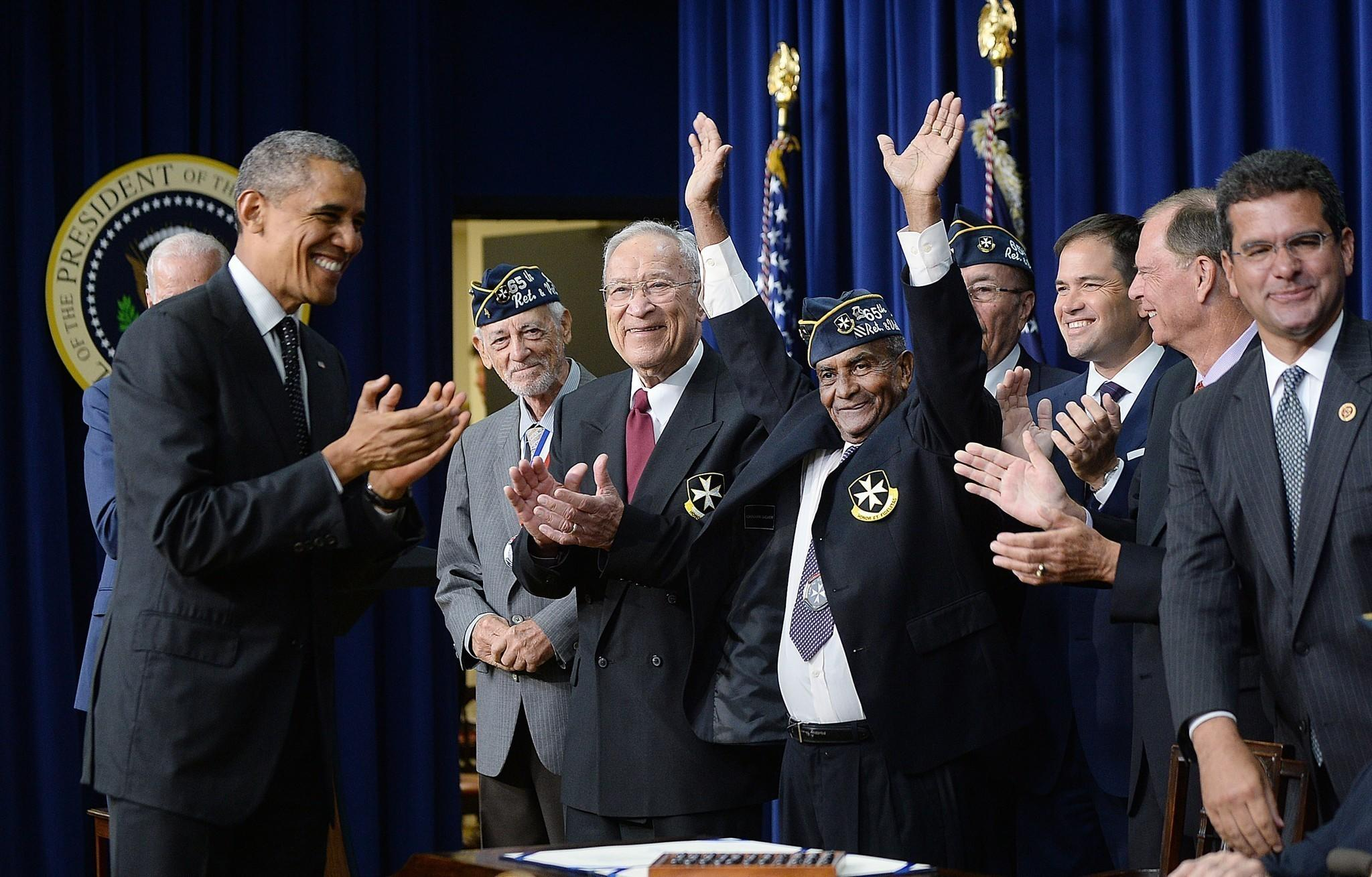 U.S. President Barack Obama signs H.R. 1726 to award a Congressional Gold Medal to the 65th Infantry Regiment, known as the Borinqueneers in the South Court Auditorium of the White House on June 10, 2014 in Washington, D.C.
