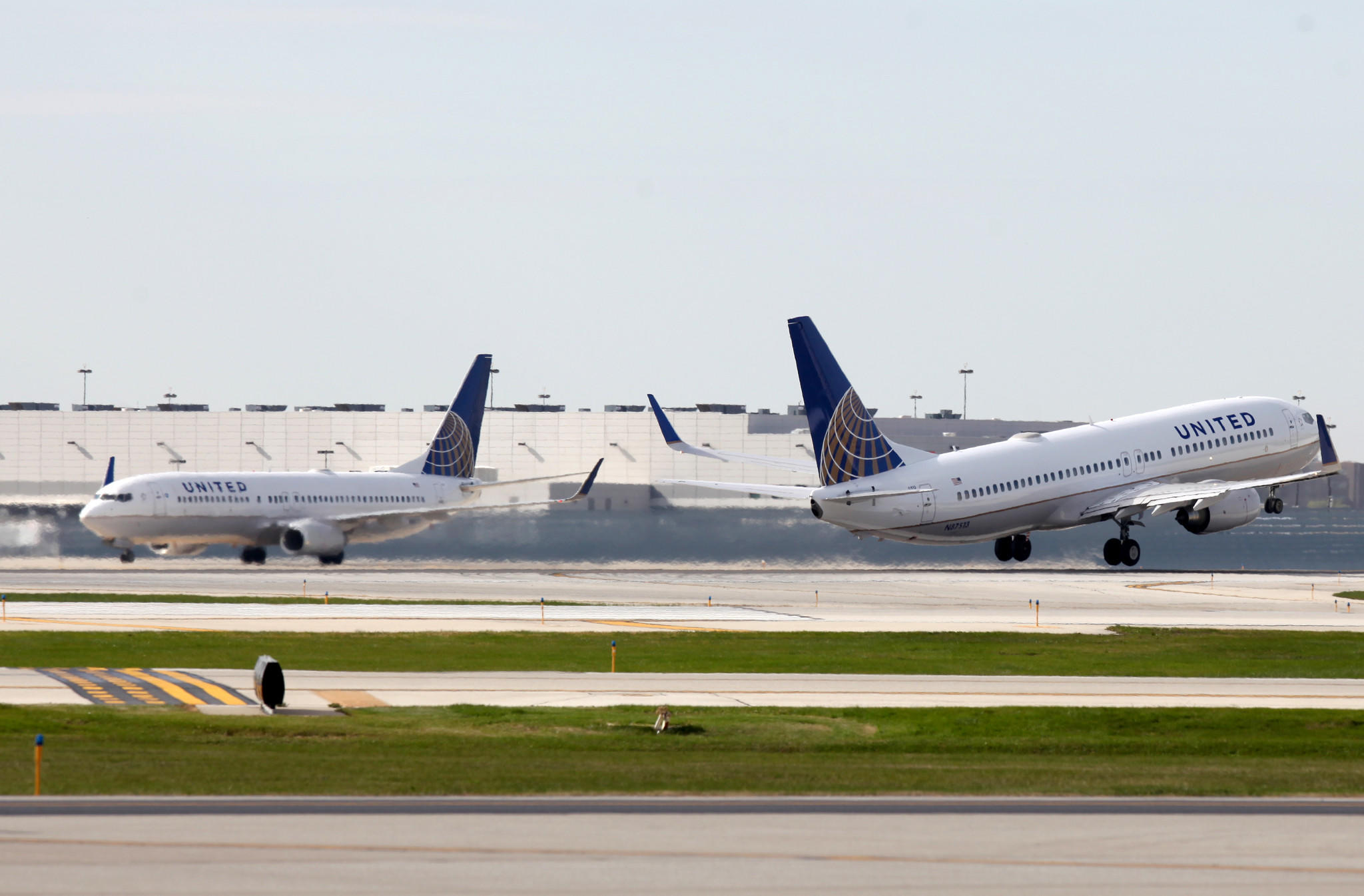 United Airlines flight takes off as another lands at Chicago O'Hare International Airport in Chicago, Friday, Oct. 25, 2013.