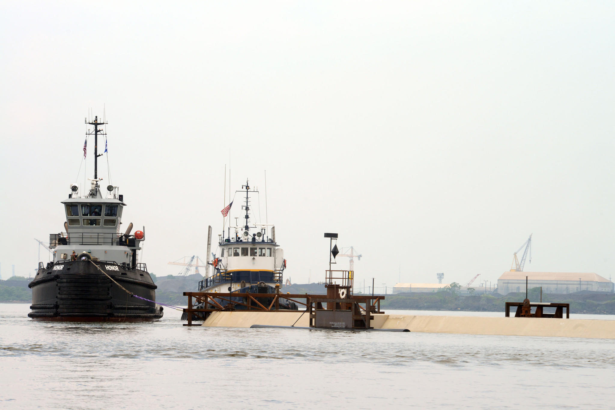 The tugboat Honor assists in the towing of a section of the Midtown Tunnel that connects Portsmouth and Norfolk, Va., Tuesday, June 10, 2014, near Sparrows Point, Maryland. Crews aboard two 25-foot Response Boat - Smalls from Coast Guard Station Curtis Bay, Maryland escorted the tugs to the Bay Bridge as the tugs towed the section down the Chesapeake Bay to the Portsmouth Marine Terminal, where it will await placement in the Elizabeth River this fall. ORG XMIT: U.S. Coast Guard