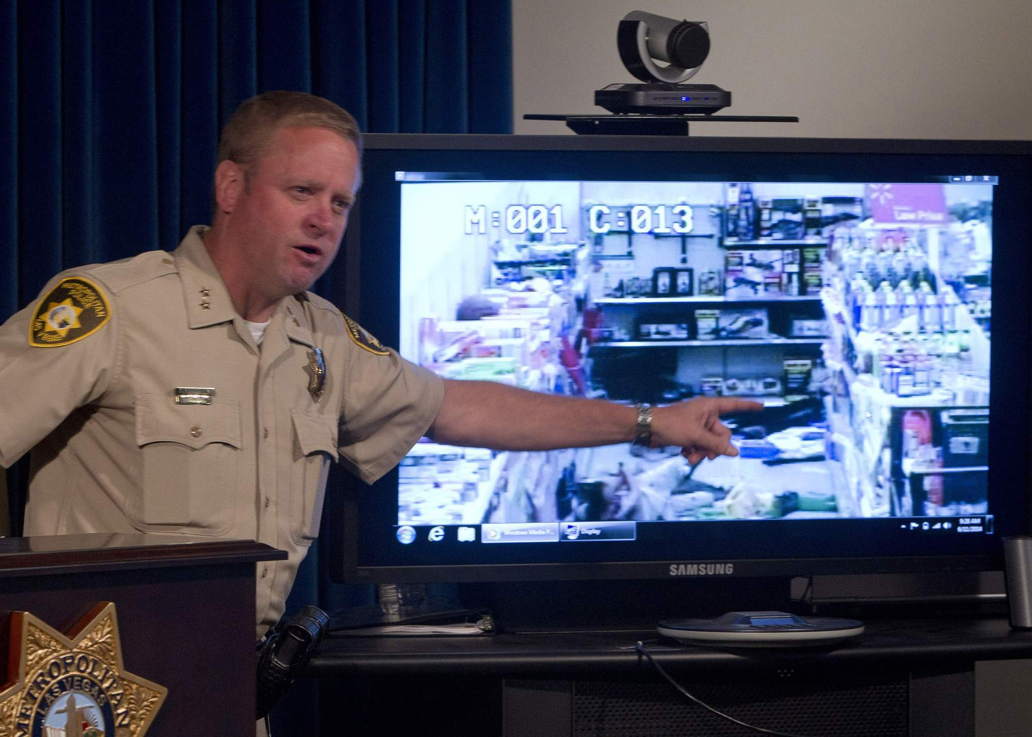 Assistant Sheriff Kevin McMahill points to Wal-Mart store surveillance video of shooting suspects Jerad Miller, 31, and his wife, Amanda Miller, 22, during a news conference at Las Vegas Metro Police headquarters in Las Vegas, Nevada June 11, 2014.