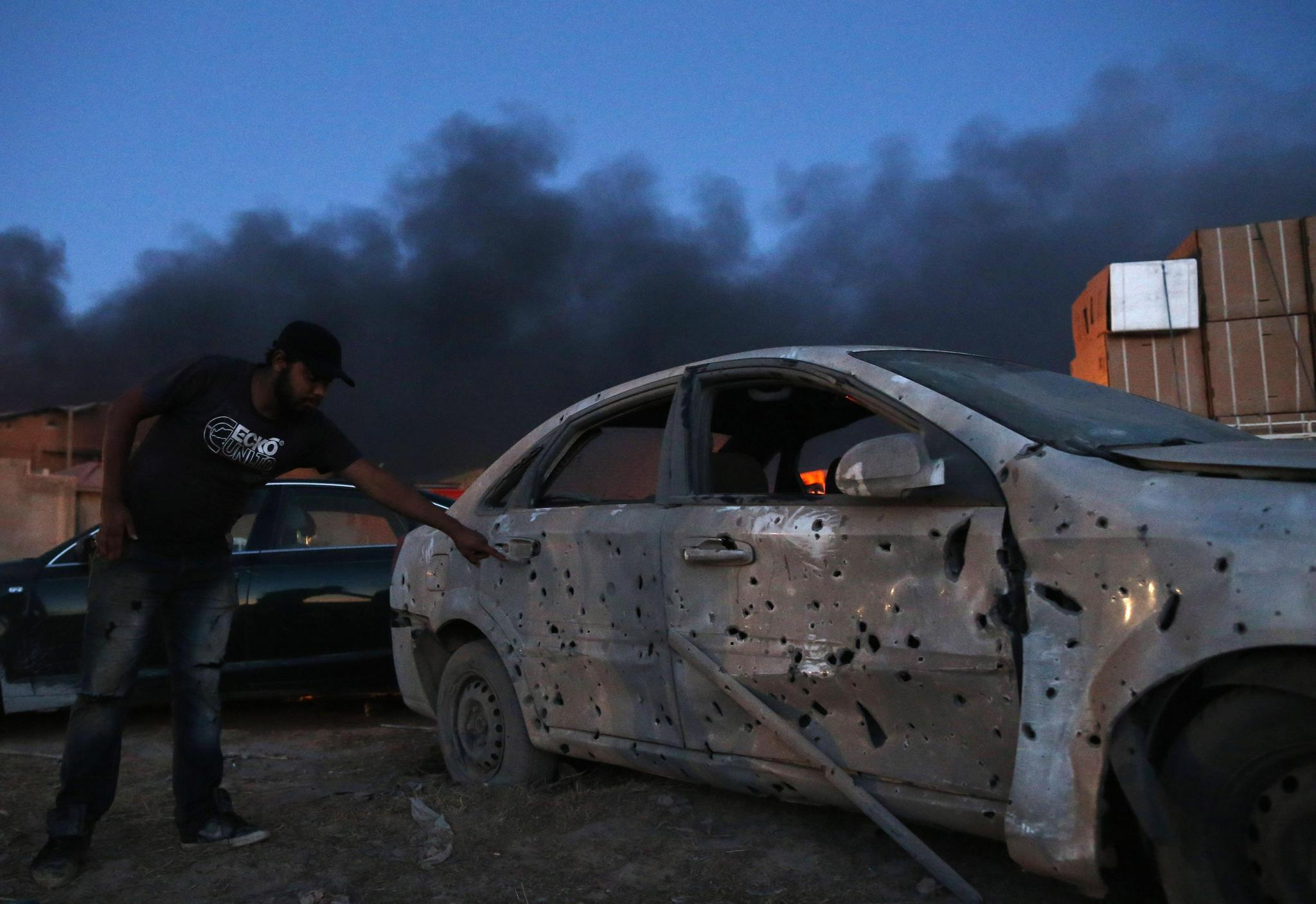 A man points to a damaged car, parked near warehouses that according to local media reports were targeted by Grad rockets fired by irregular forces loyal to former Libyan army general Khalifa Haftar in Benghazi June 5, 2014. The attack is part of a campaign by irregular forces loyal to Haftar who earlier in May launched operations against Islamist militants.