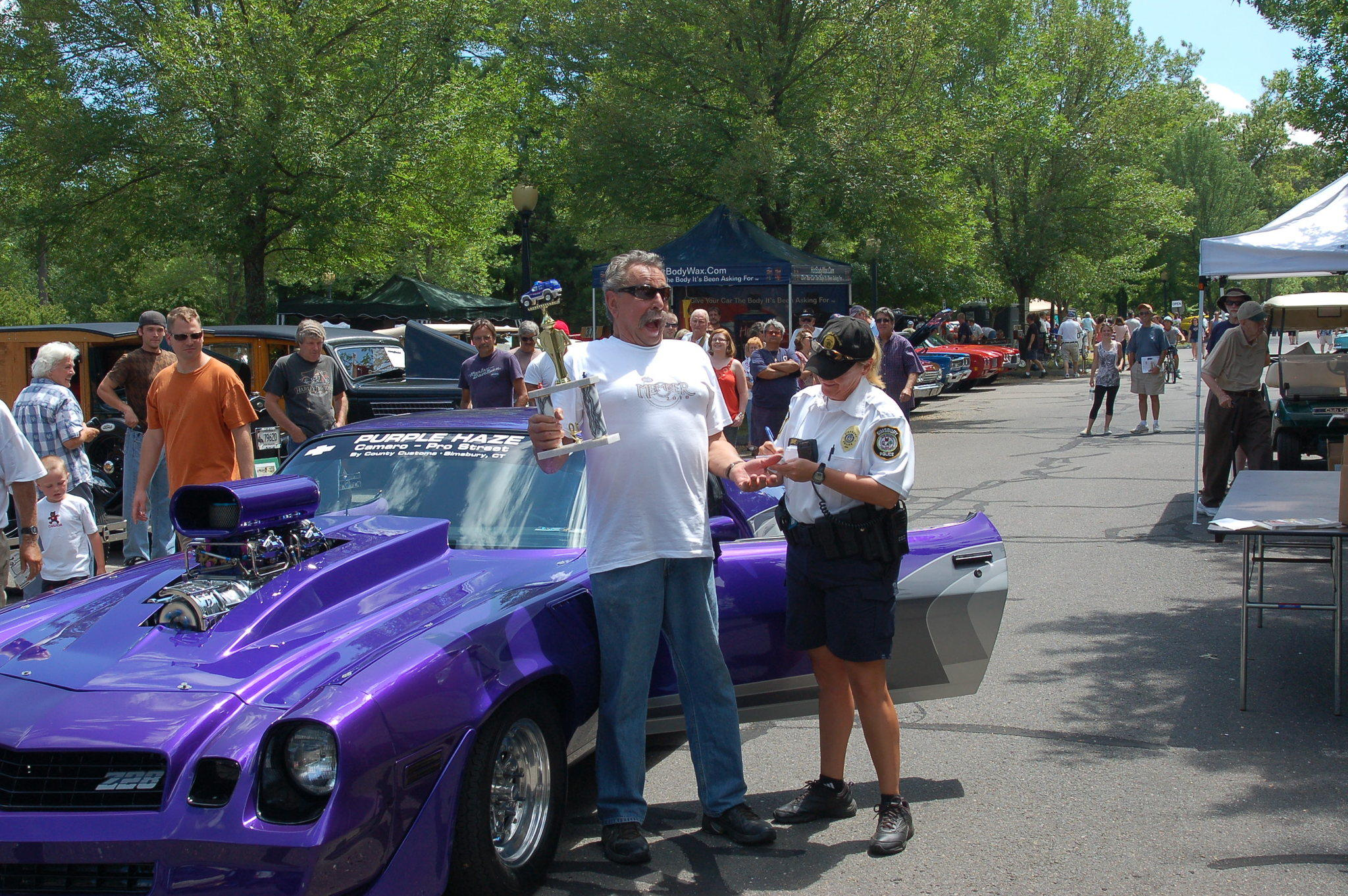 "Joe Pozzato receives the ""Most Likely to get Pulled Over by Police"" Award from the Simsbury Officer on duty, at a previous Charity Benefit Car Show."