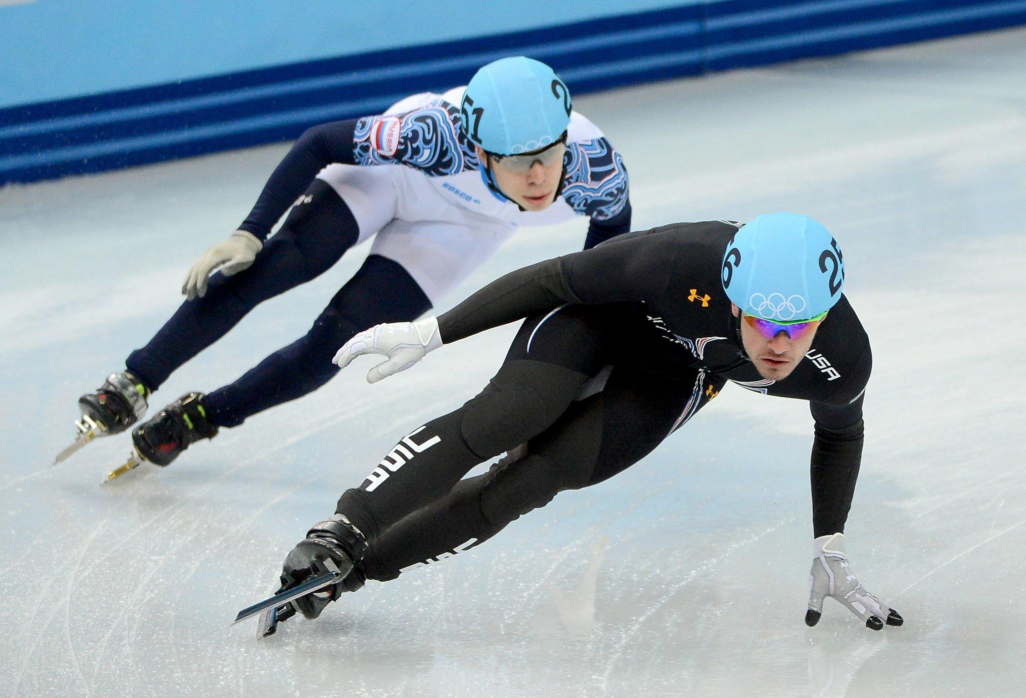 The USA's Eduardo Alvarez leads Russia's Semen Elistratov during the short track men's 5000m relay final at the Iceberg Skating Palace at the Winter Olympics in Sochi.