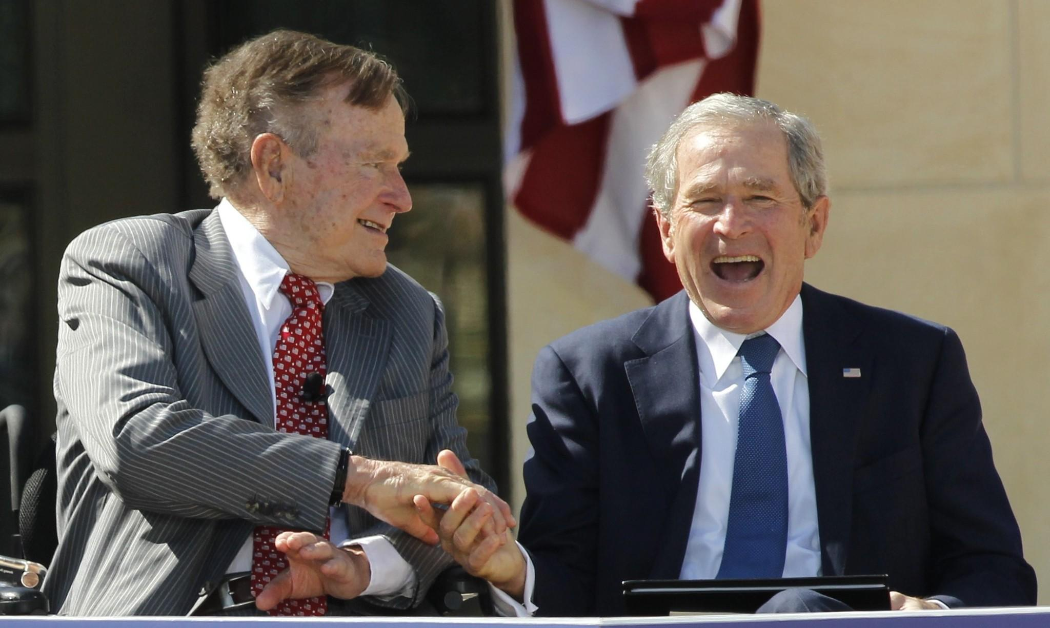 Father and son, and former U.S. Presidents, George H.W. Bush (L) and George W. Bush, shake hands at the dedication for the George W. Bush Presidential Center on the campus of Southern Methodist University in Dallas, Texas April 25, 2013.