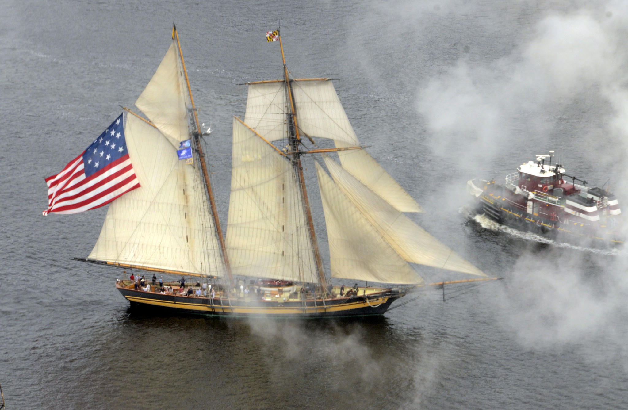 Tall ships leave the Inner Harbor ending the Star Spangled Sailabration, with the Pride of Baltimore II leading the way.