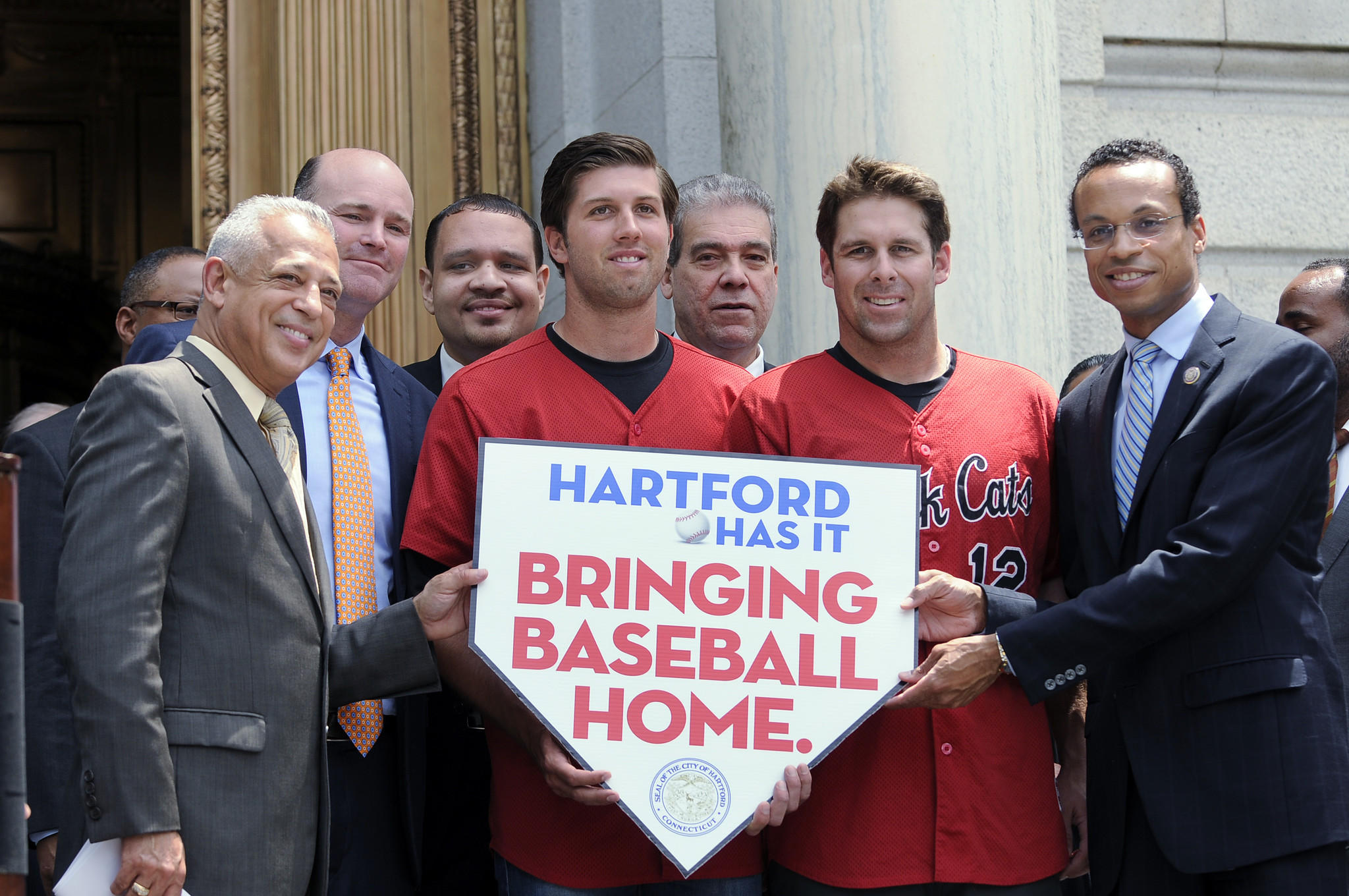 Holding a sign reading, Hartford Has It, Bringing Baseball Home, are Hartford Mayor Pedro Segarra, Rock Cats owner Josh Solomon, Hartford Common Council member Raul DeJesus, Rock Cats pitcher Pat Dean, State Rep. Edwin Vargas, Rock Cats infielder Nate Hanson, and Common Council President Shawn Woodin (l-r) after a press conference announcing the city's plan to build a stadium for the New Britain Rock Cats in Hartford. CLOE POISSON|cpoisson@courant.com ORG XMIT: B583778881Z.1