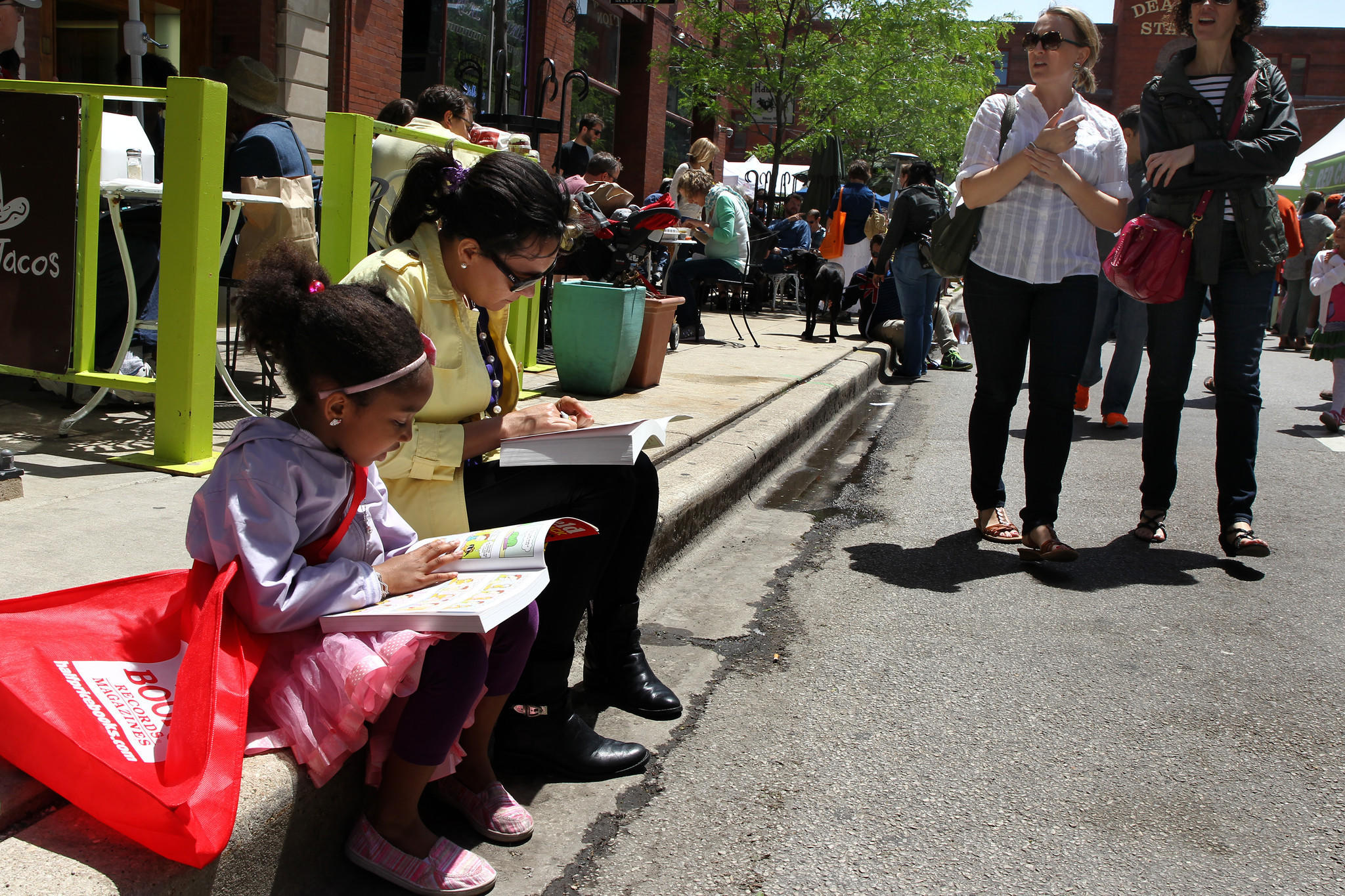 Marlene Silva and her daughter Jacqueline, 6, sit on a curb and start reading some of their book purchases at Printers Row Lit Fest.