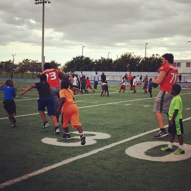 Miami players Calvin Heurtelou and Anthony Chickillo go through drills with children during the Hurricanes' Deserve Victory camp.