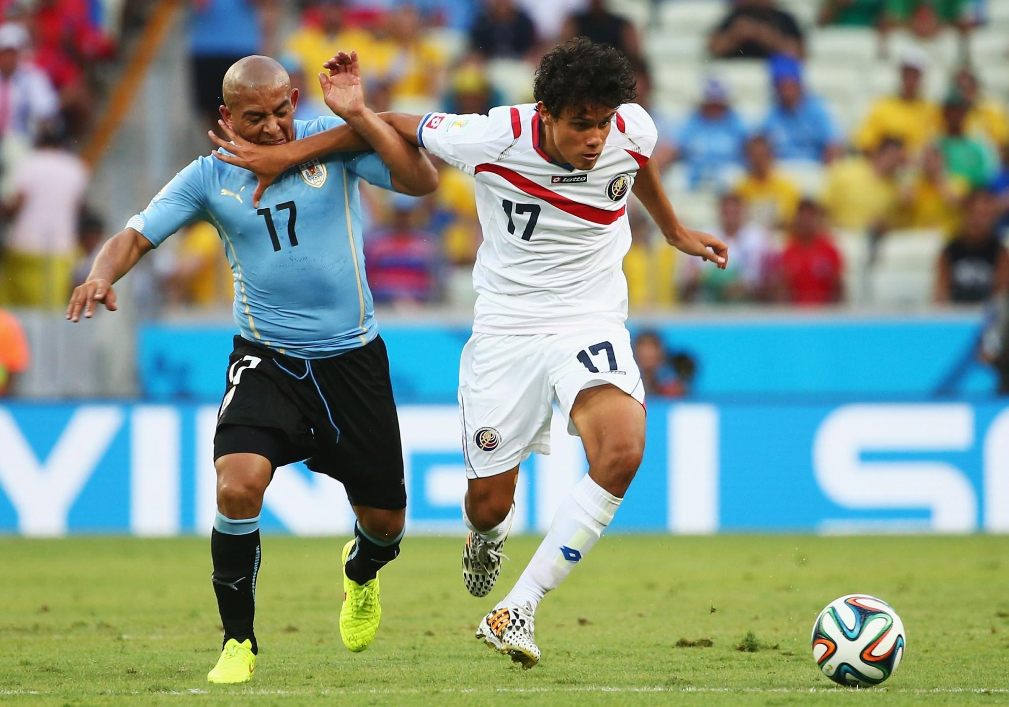 Yeltsin Tejeda of Costa Rica holds off a challenge by Egidio Arevalo Rios of Uruguay during the 2014 FIFA World Cup Brazil Group D match.