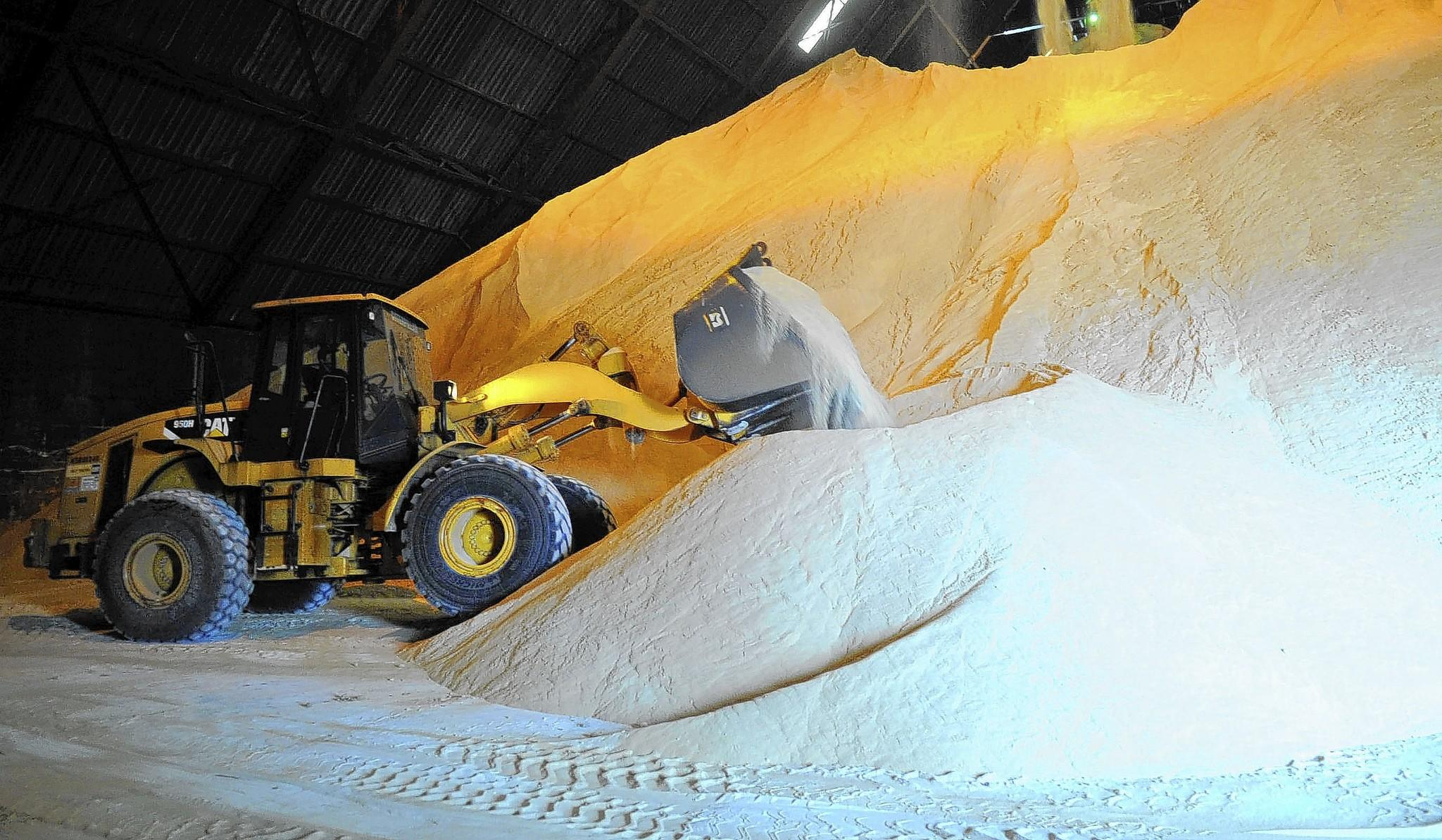 A front end loader operator moves mountain of sugar like sand inside the sugar warehouse at the Port of Palm Beach.